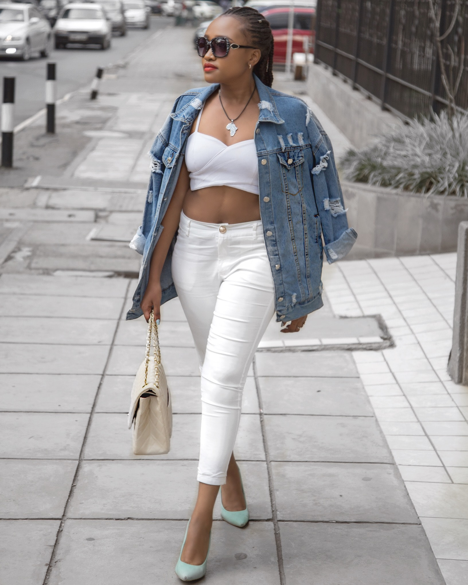 Photo of Woman Wearing White Crop Top and Denim Jacket Walking in ...