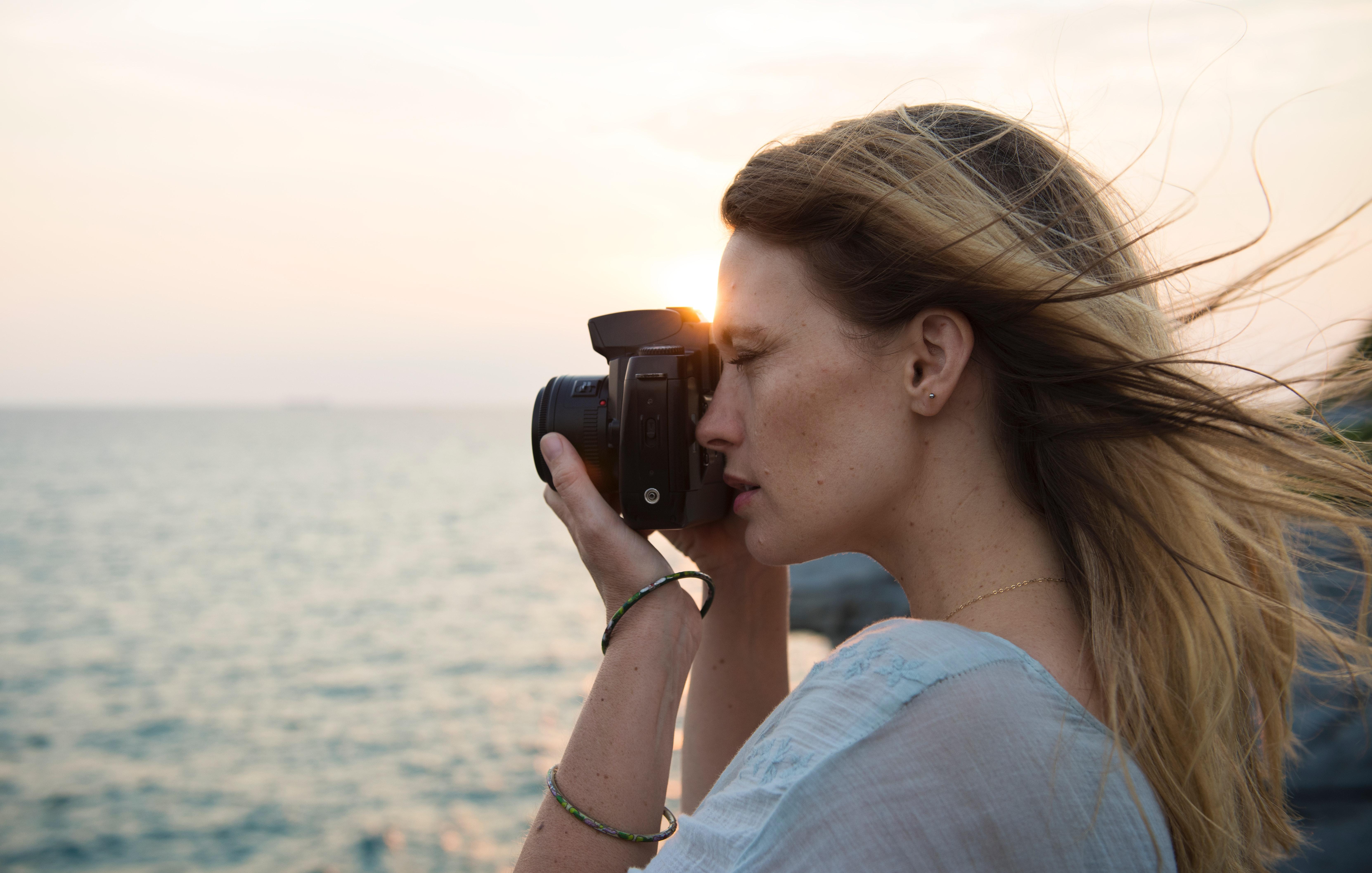 Woman holding black dslr camera photo