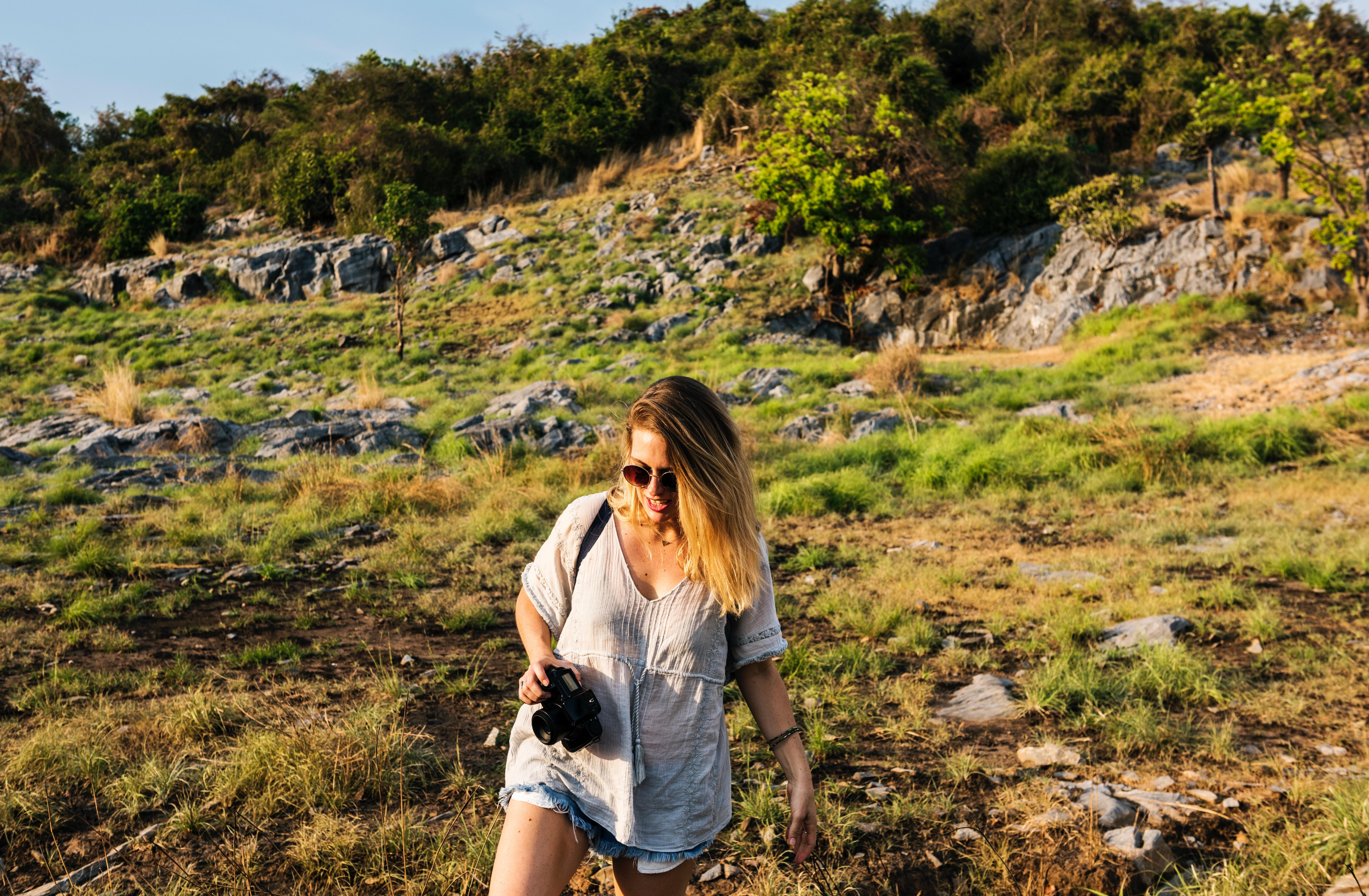 Woman holding black dslr camera near forest photo