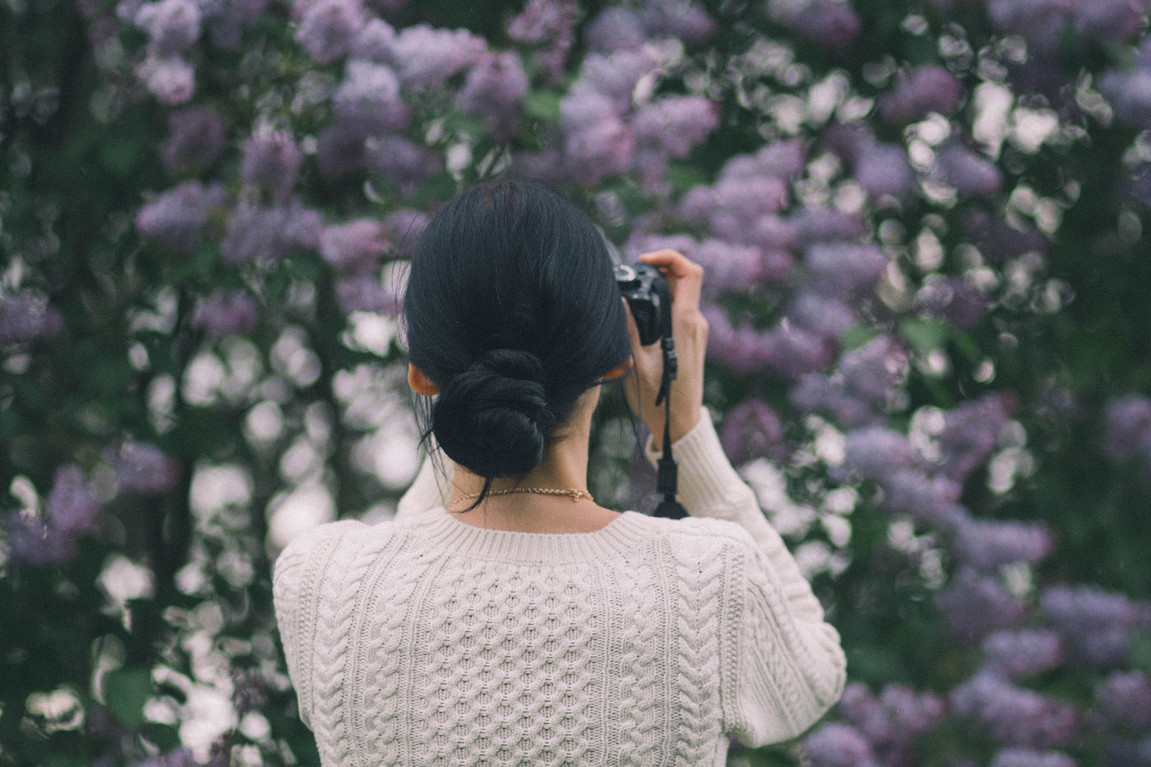 Woman holding camera taking photos of flowers