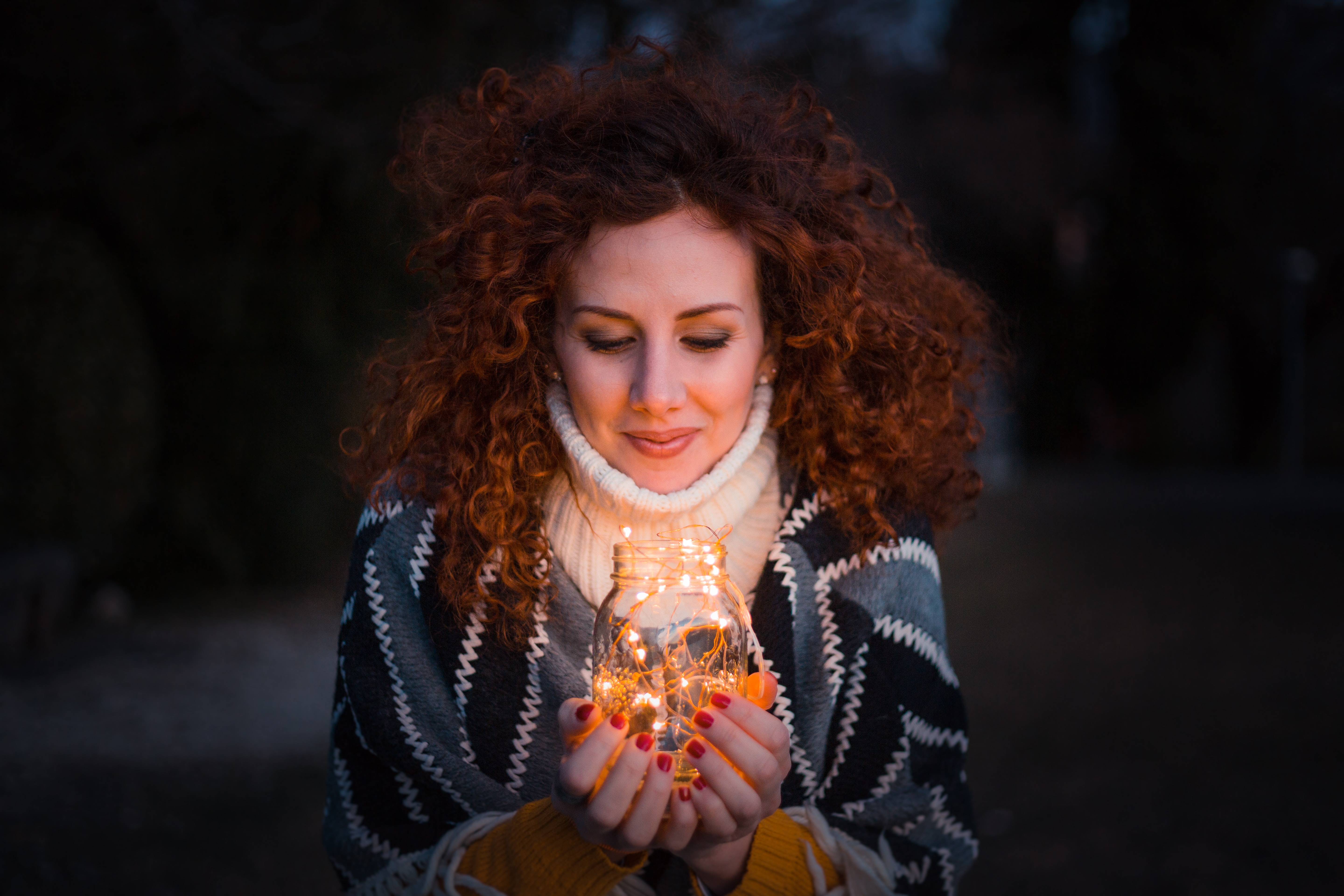 Woman holding clear glass jar filled with lights photo