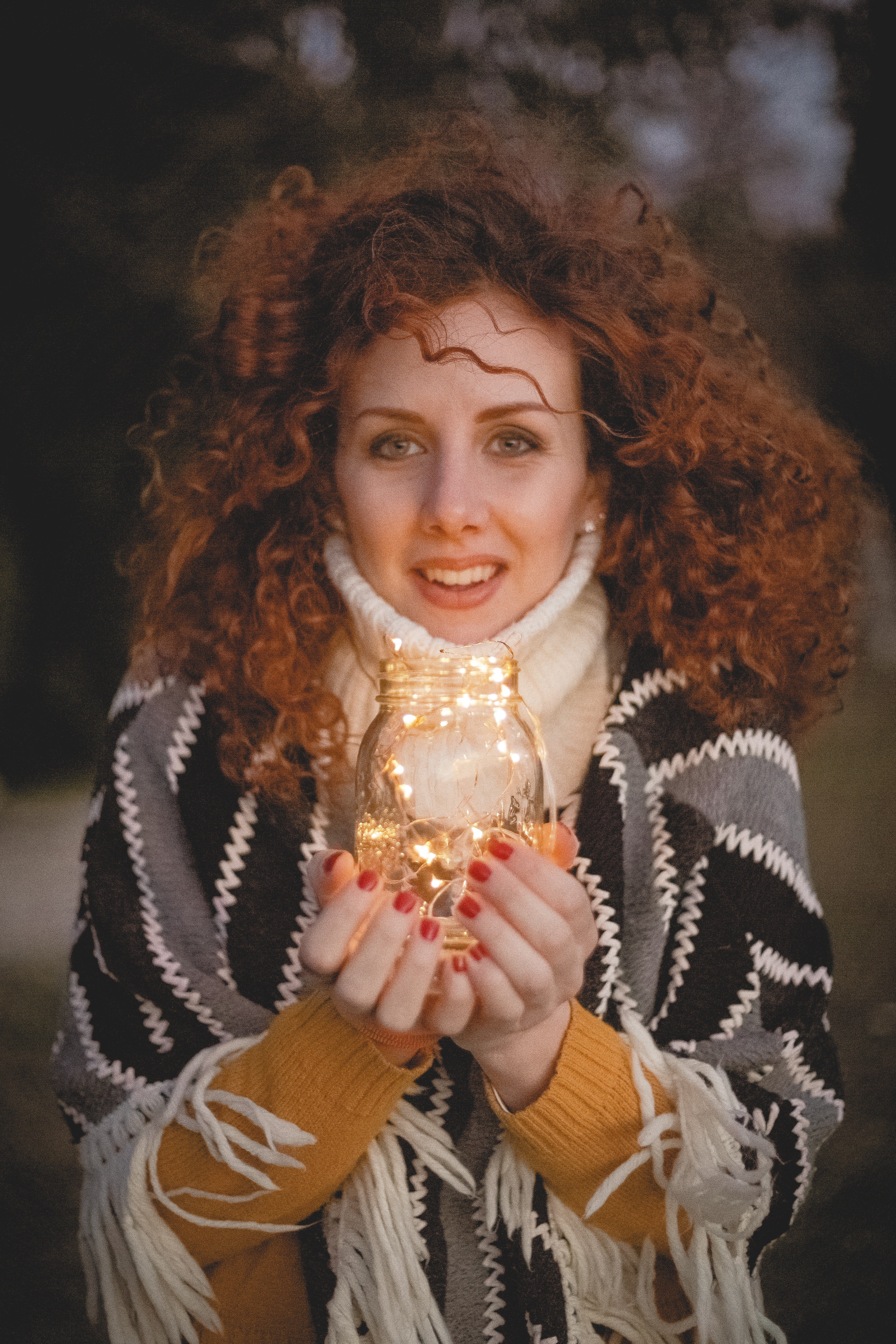 Woman holding clear glass jar with string lights photo