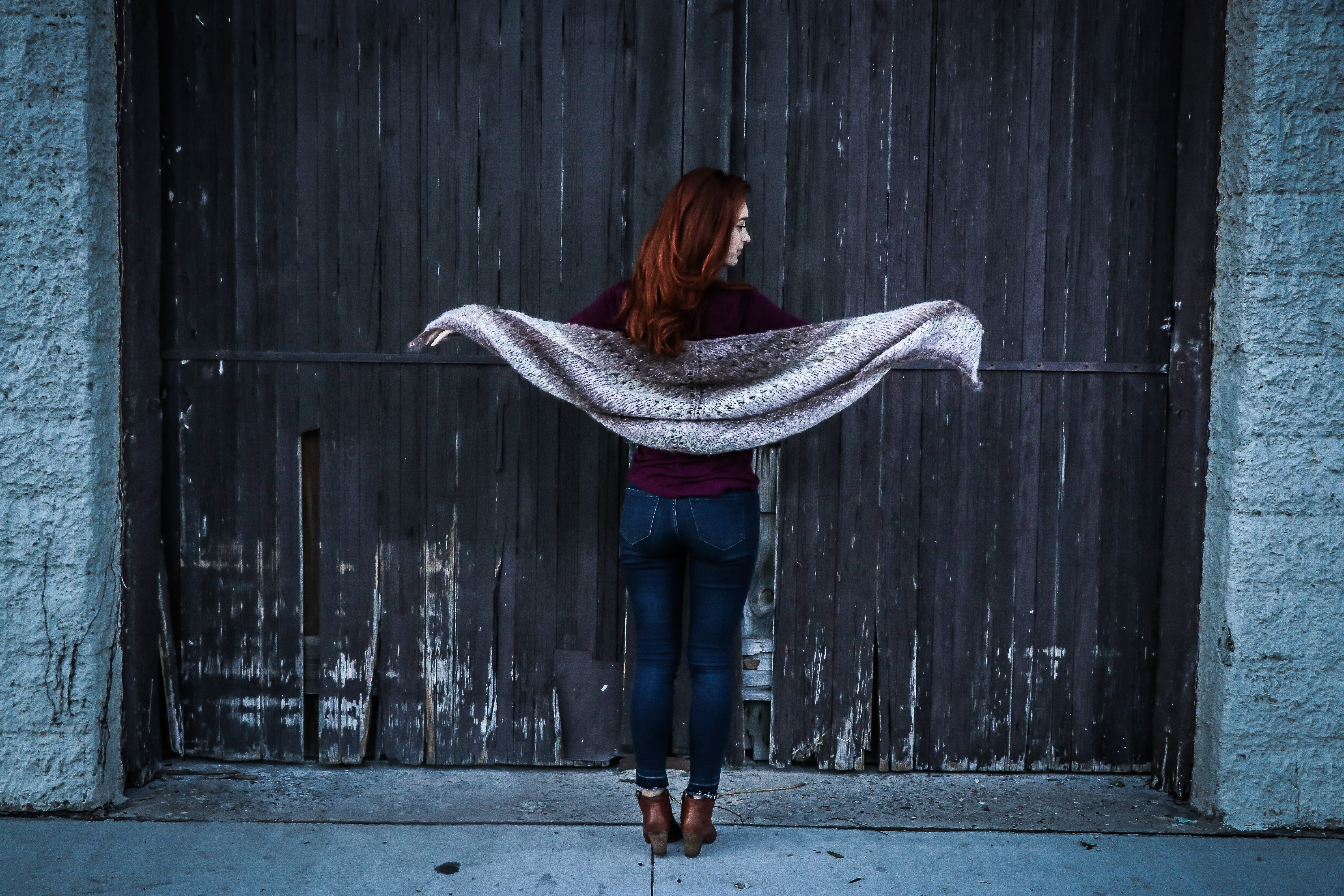 Woman holding gray shawl while spreading her arms infront of brown wooden door photo