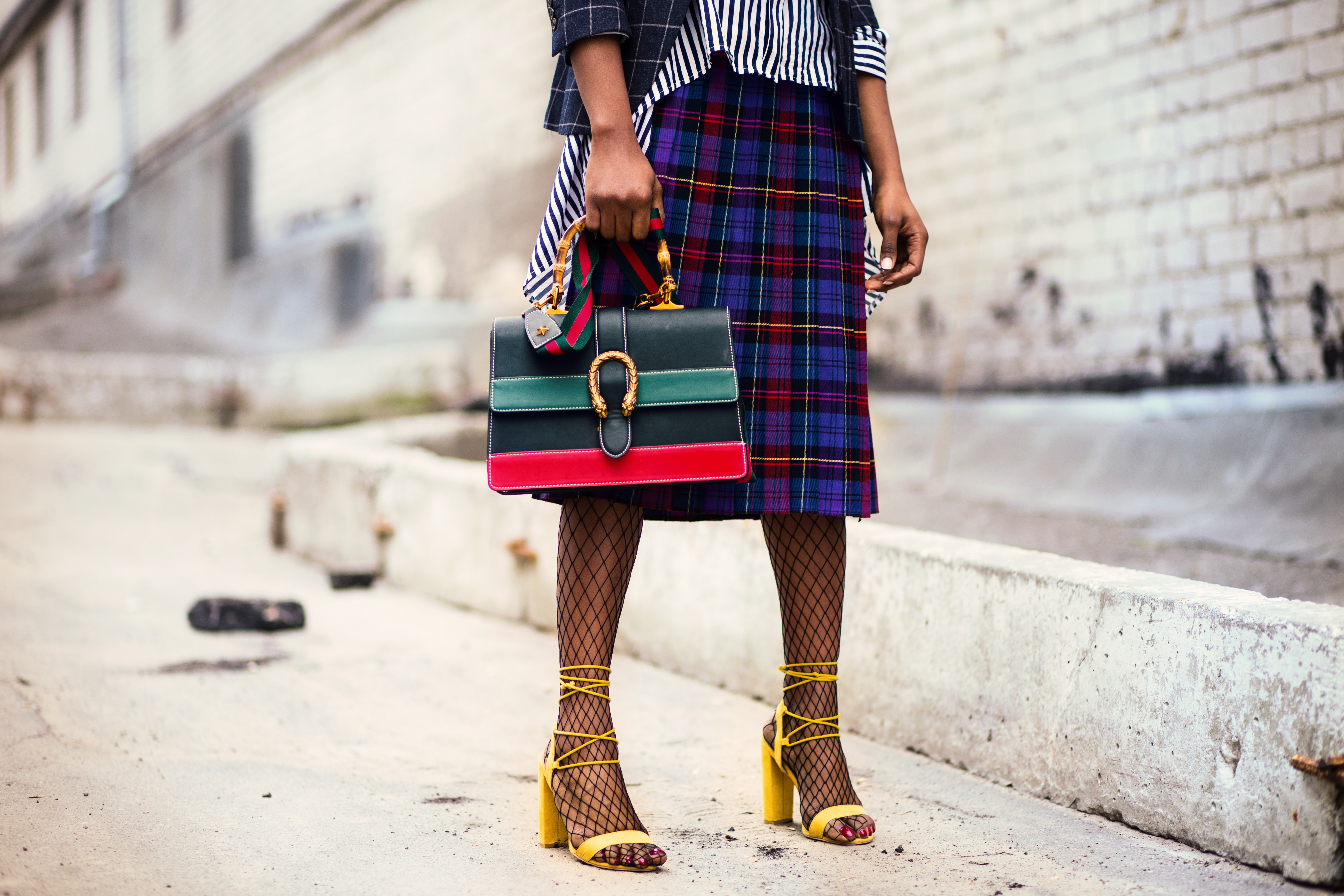 Woman holding green and red leather handbag photo