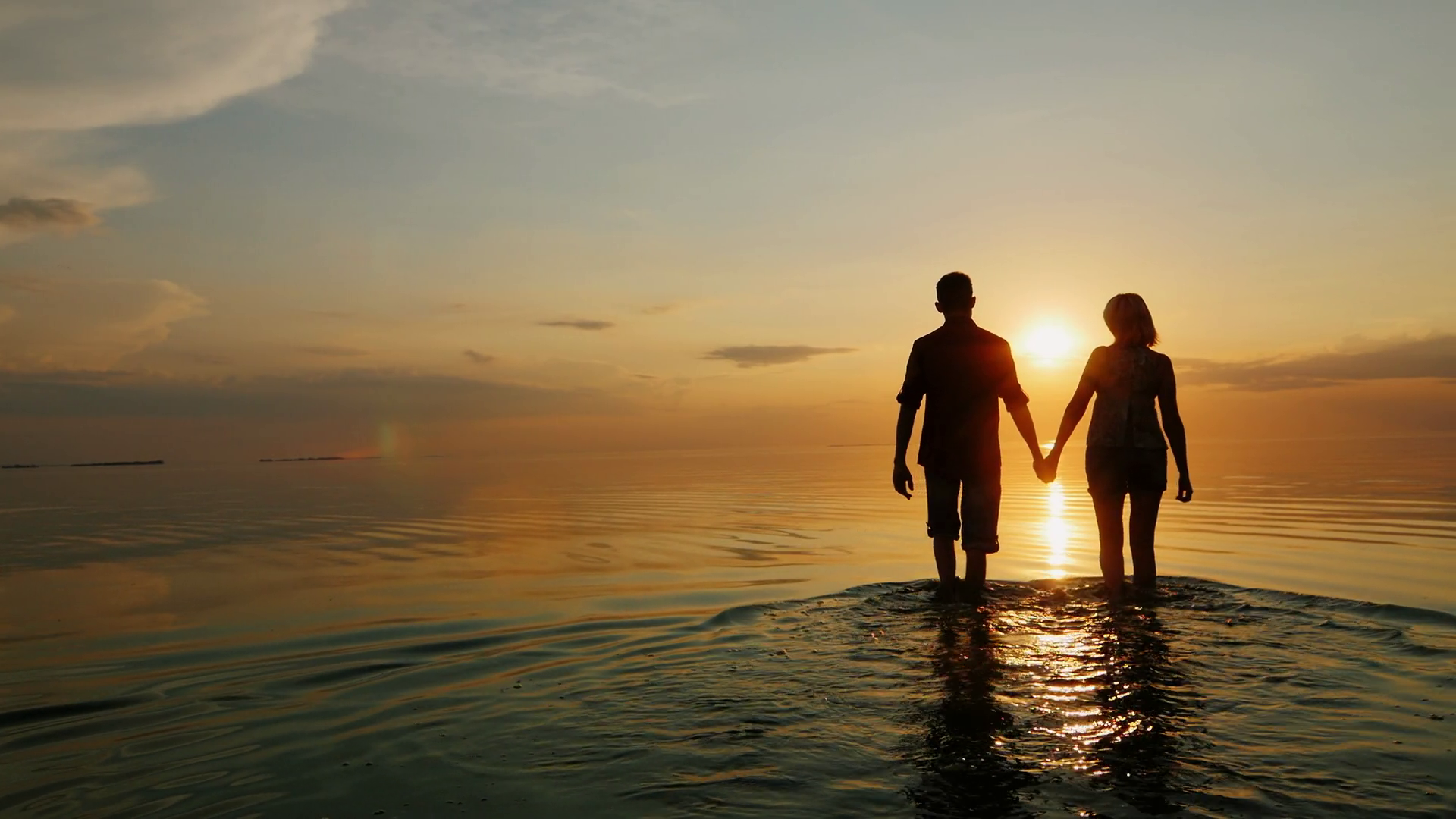 A man and a woman go to the sea at sunset, holding hands ...