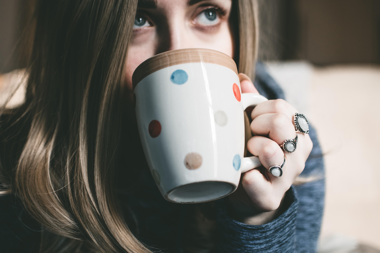 Woman holding her multicolored polka-dot ceramic mug photo