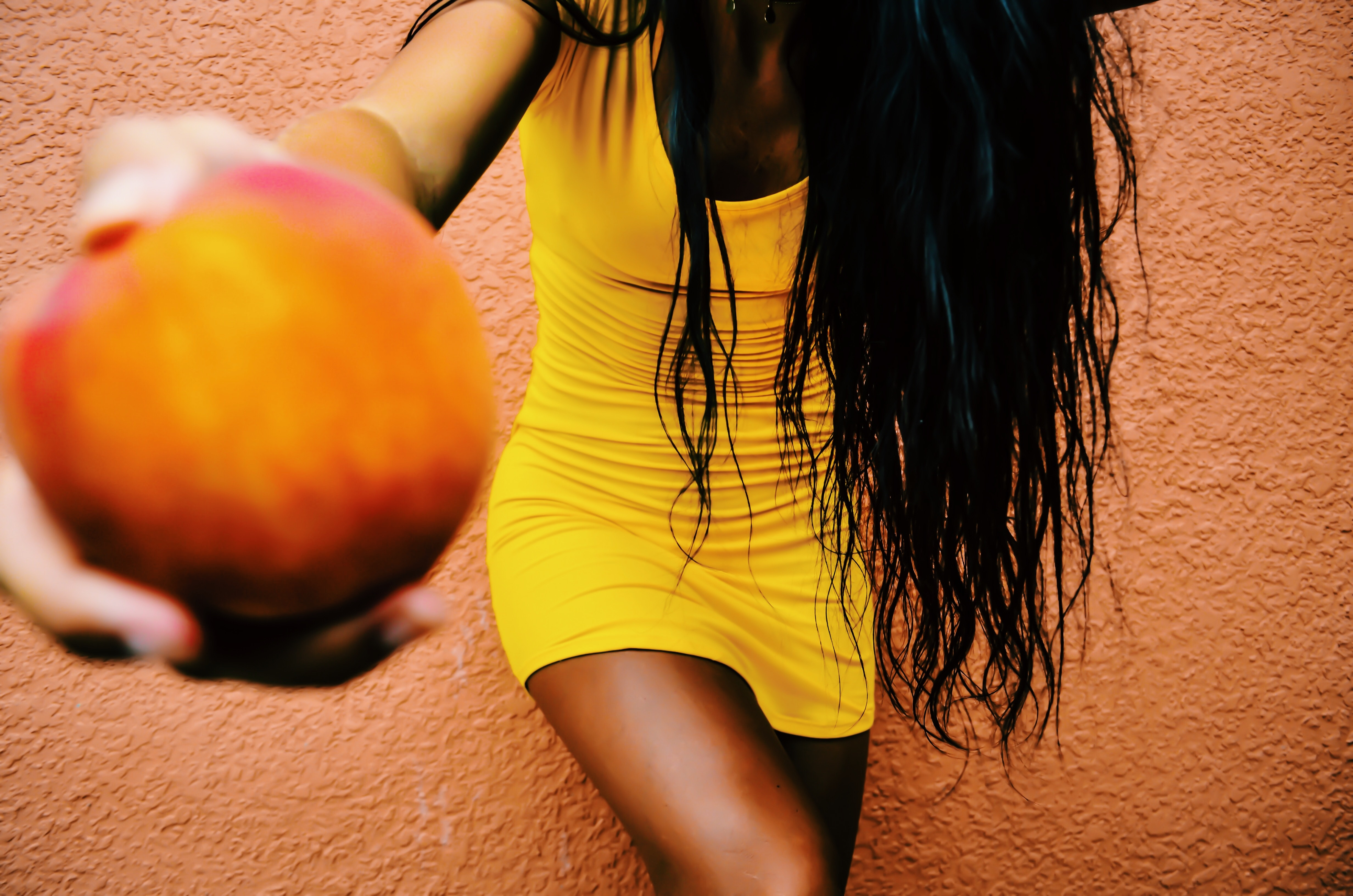 Woman holding round fruit while leaning on orange wall photo