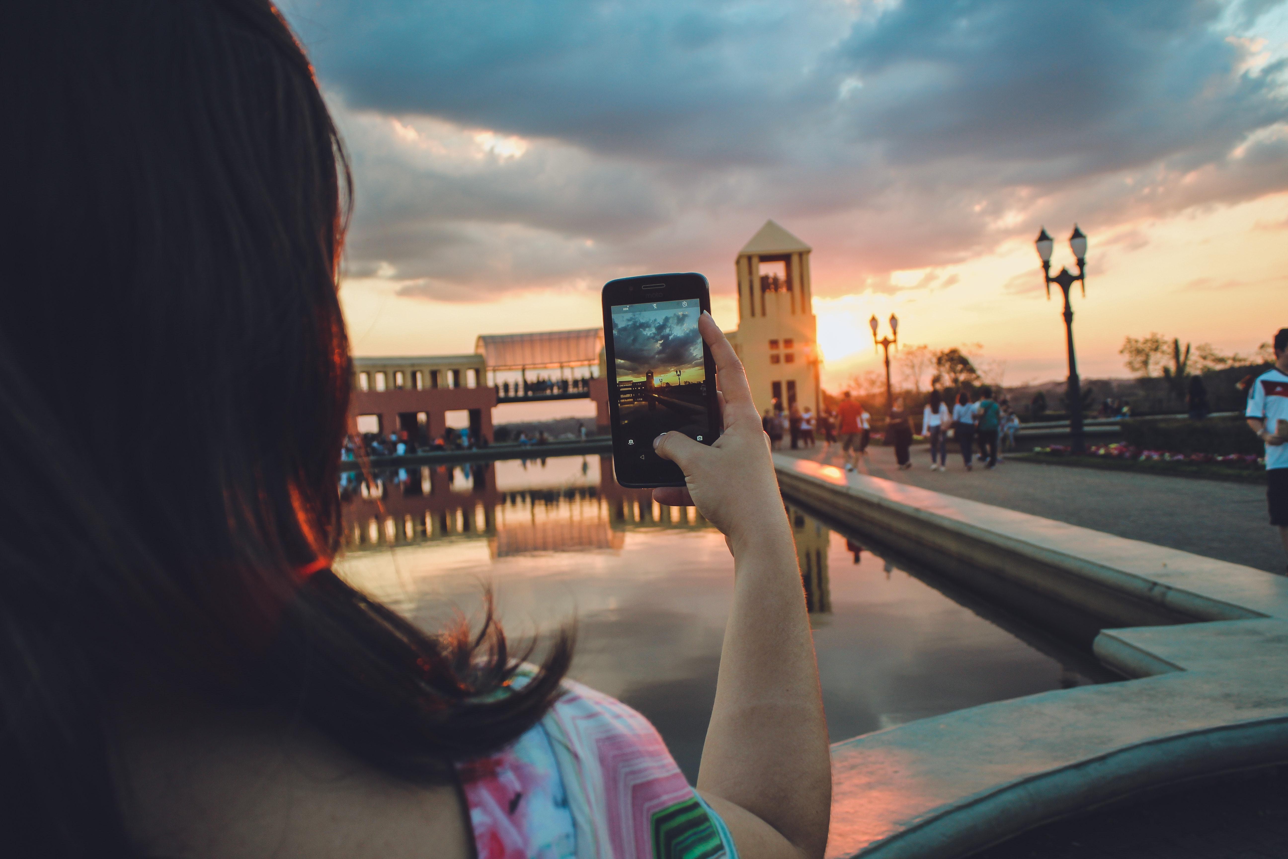Woman holding smartphone capturing sunset photo