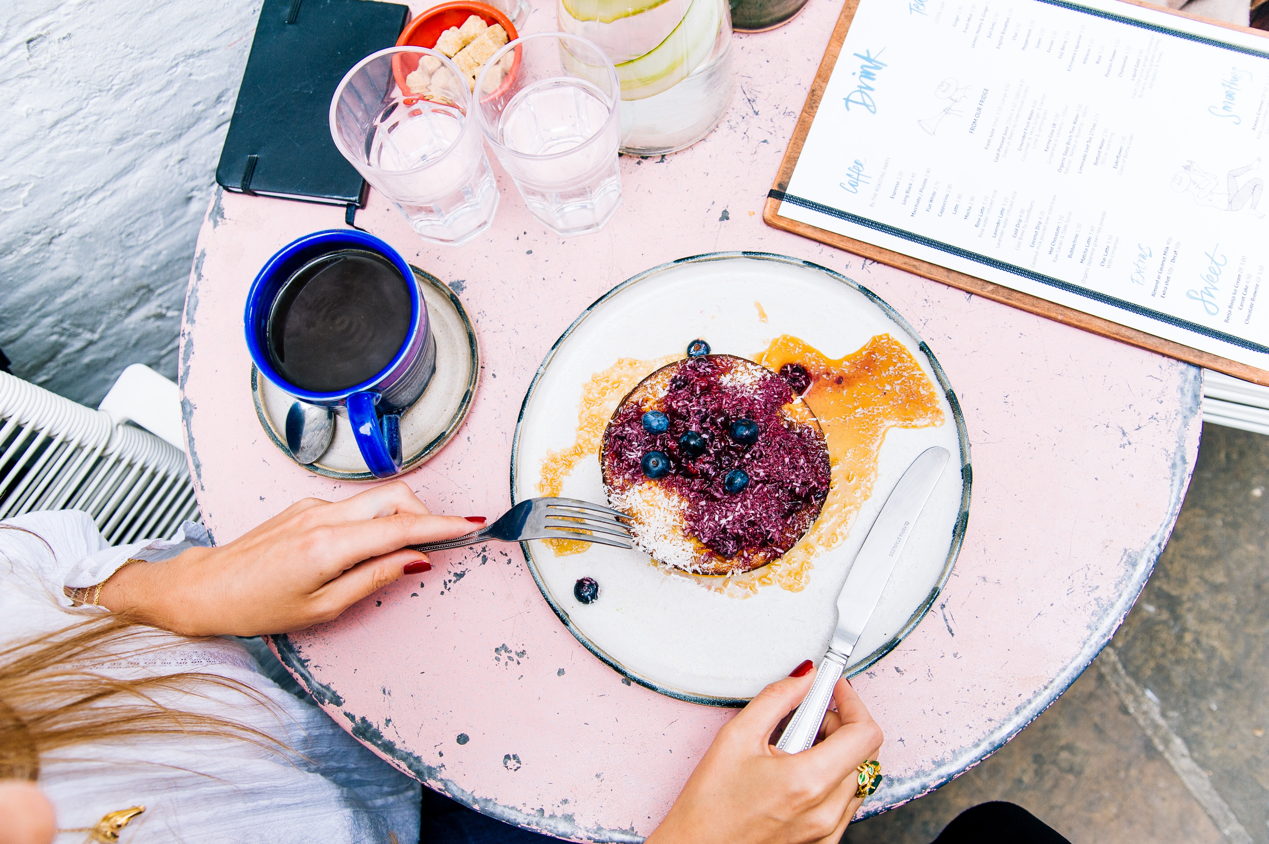 Woman Holding Spoon and Fork With Blackberries on Plate Beside Blue Ceramic Mug on White Wooden Table, Black coffee, Teaspoon, Tasty, Table, HQ Photo