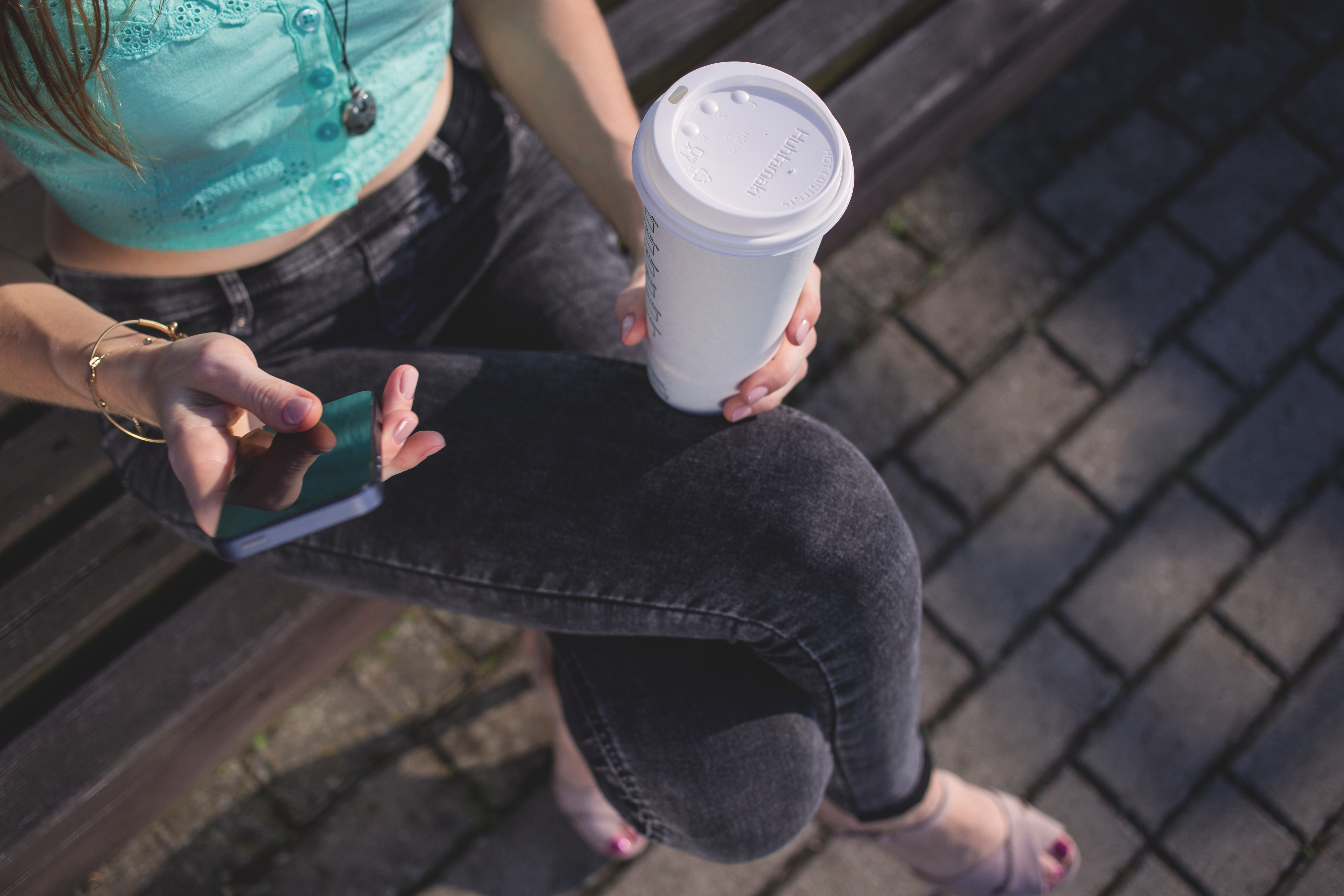 Woman holding white disposable cup and smartphone photo