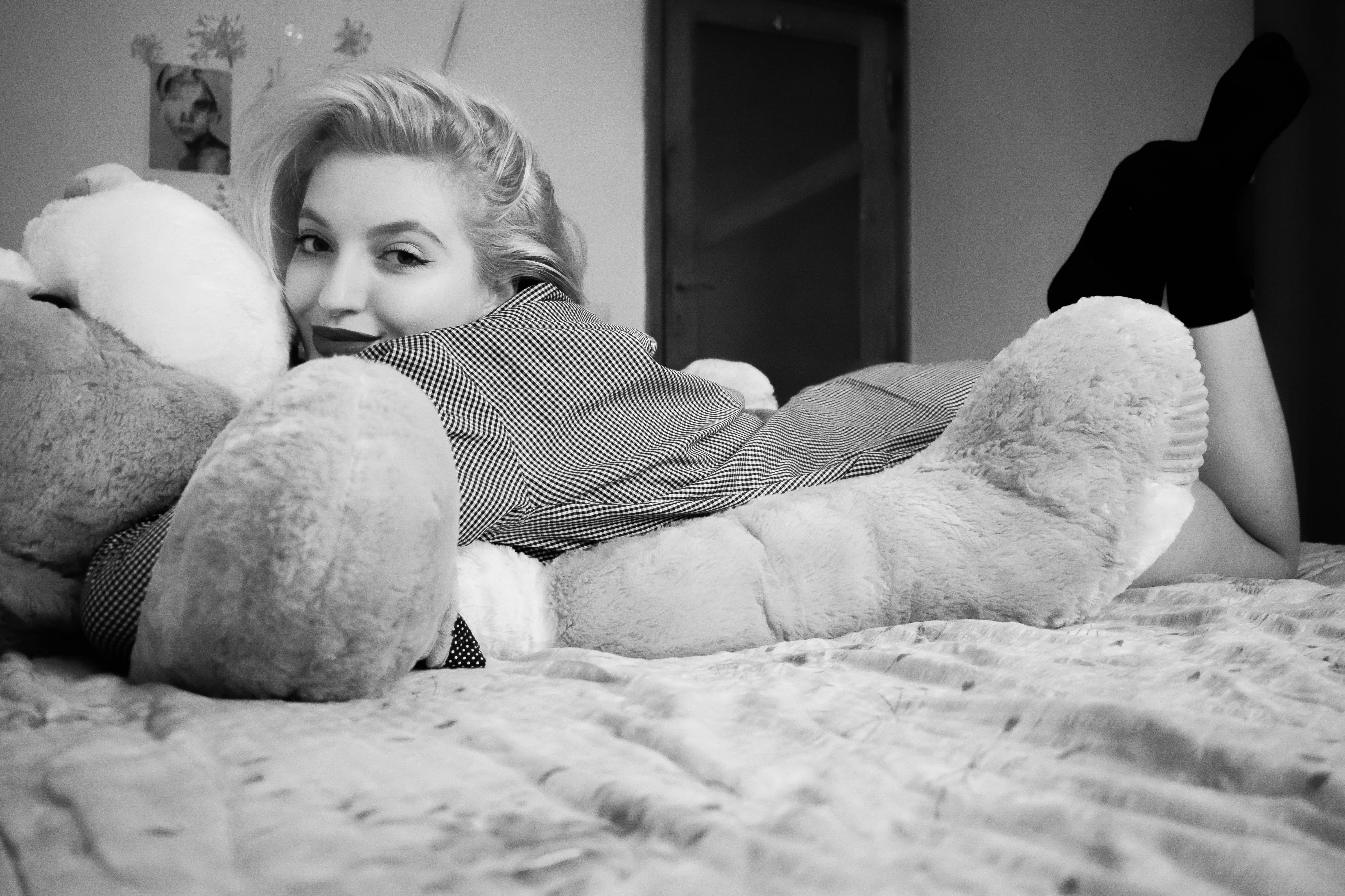 Woman hugging bear lying on bed photo
