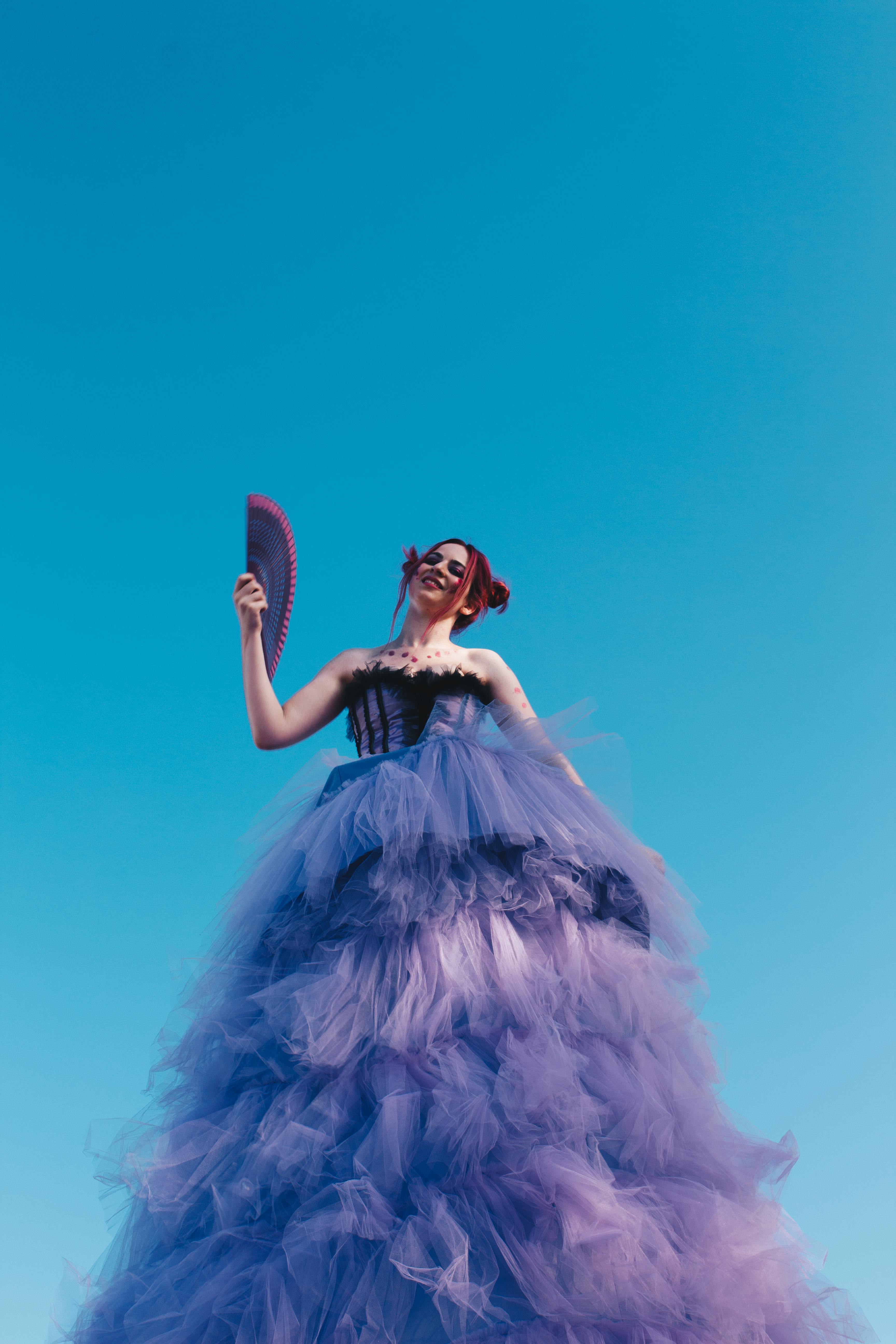 Woman in black and purple ruffle dress holding hand fan photo