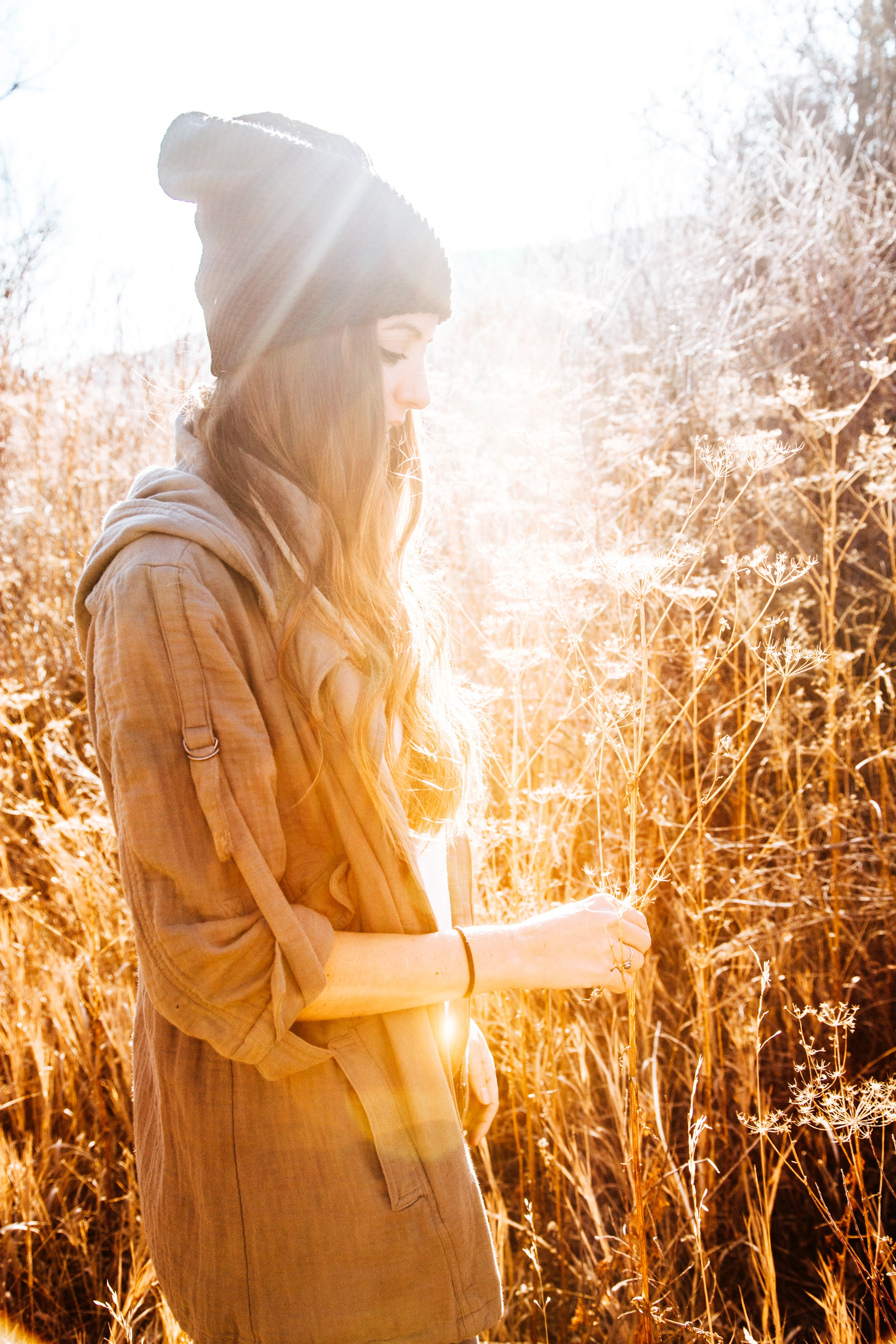 Woman in black beanie standing next to tall grass photo