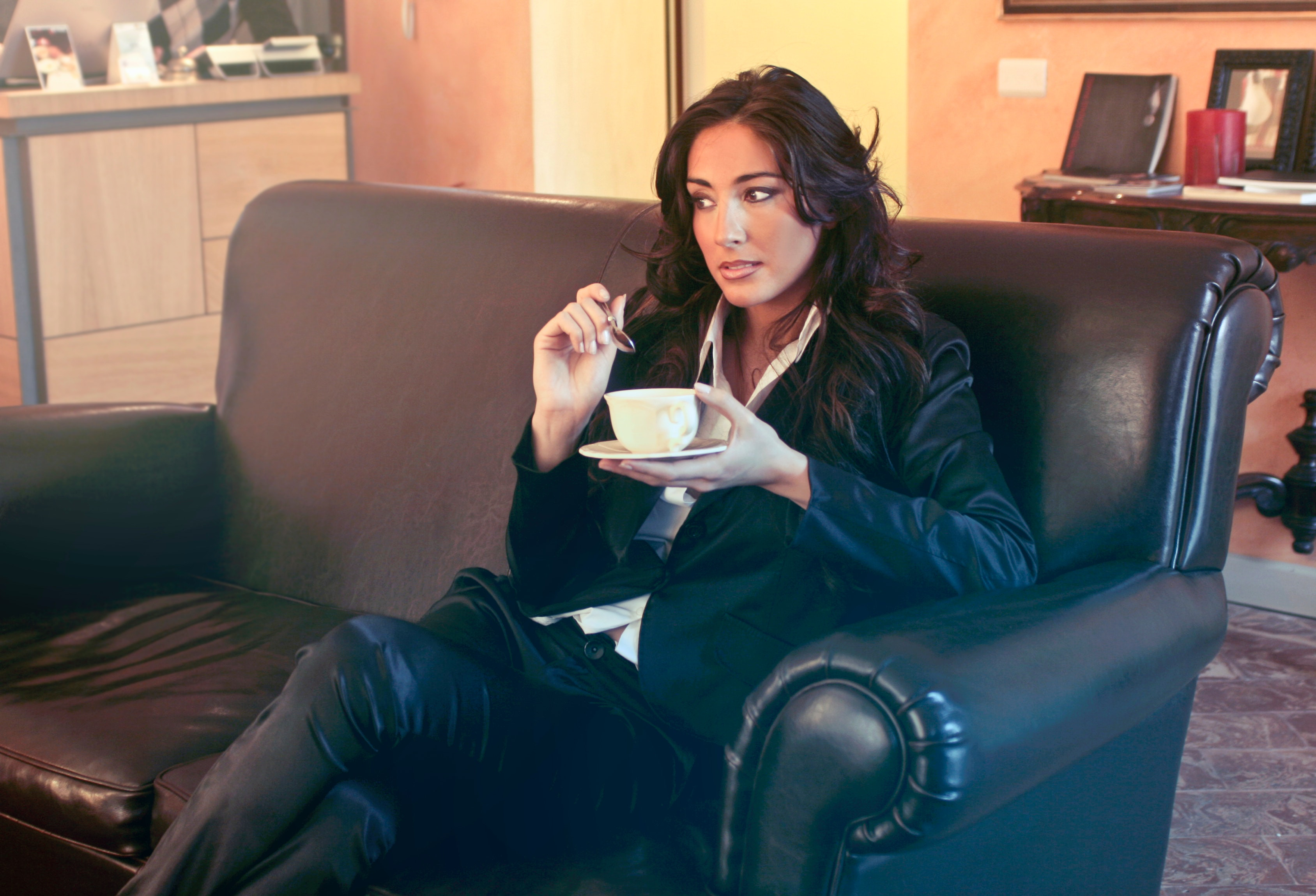 Woman in black blazer holding teacup while sits on black sofa photo