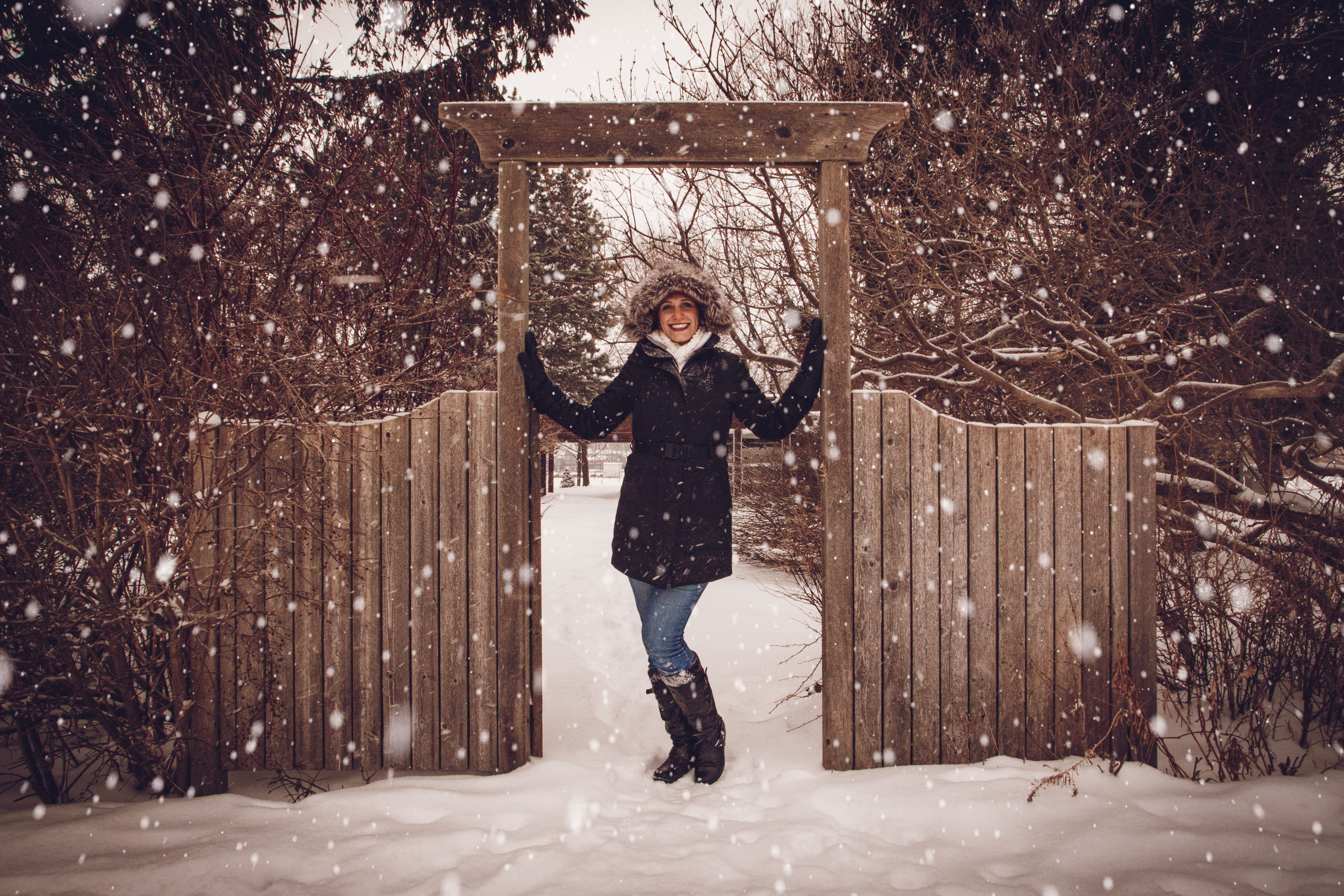Woman in black coat beside fence during snow photo