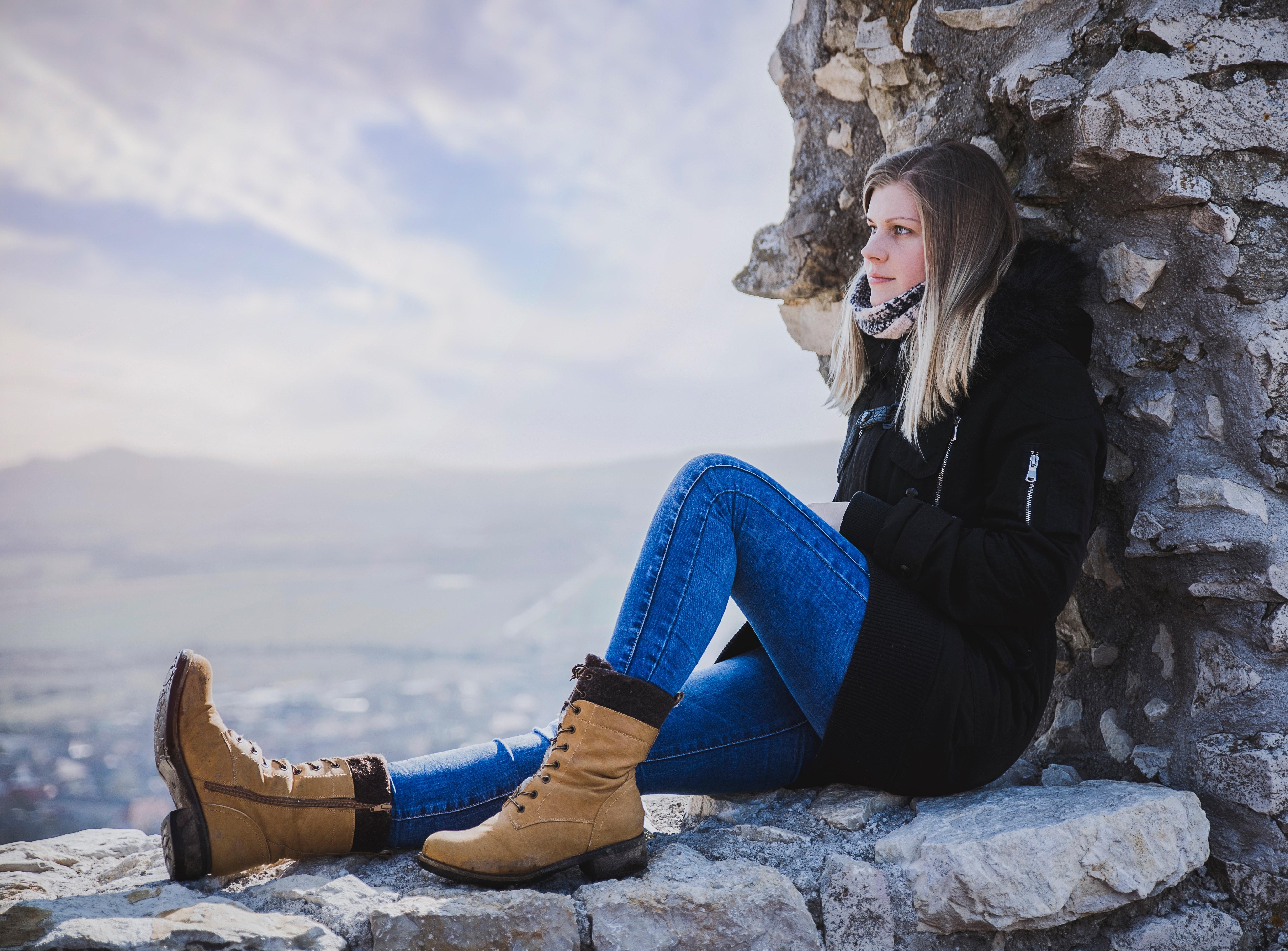 Woman in black coat sitting on rock photo