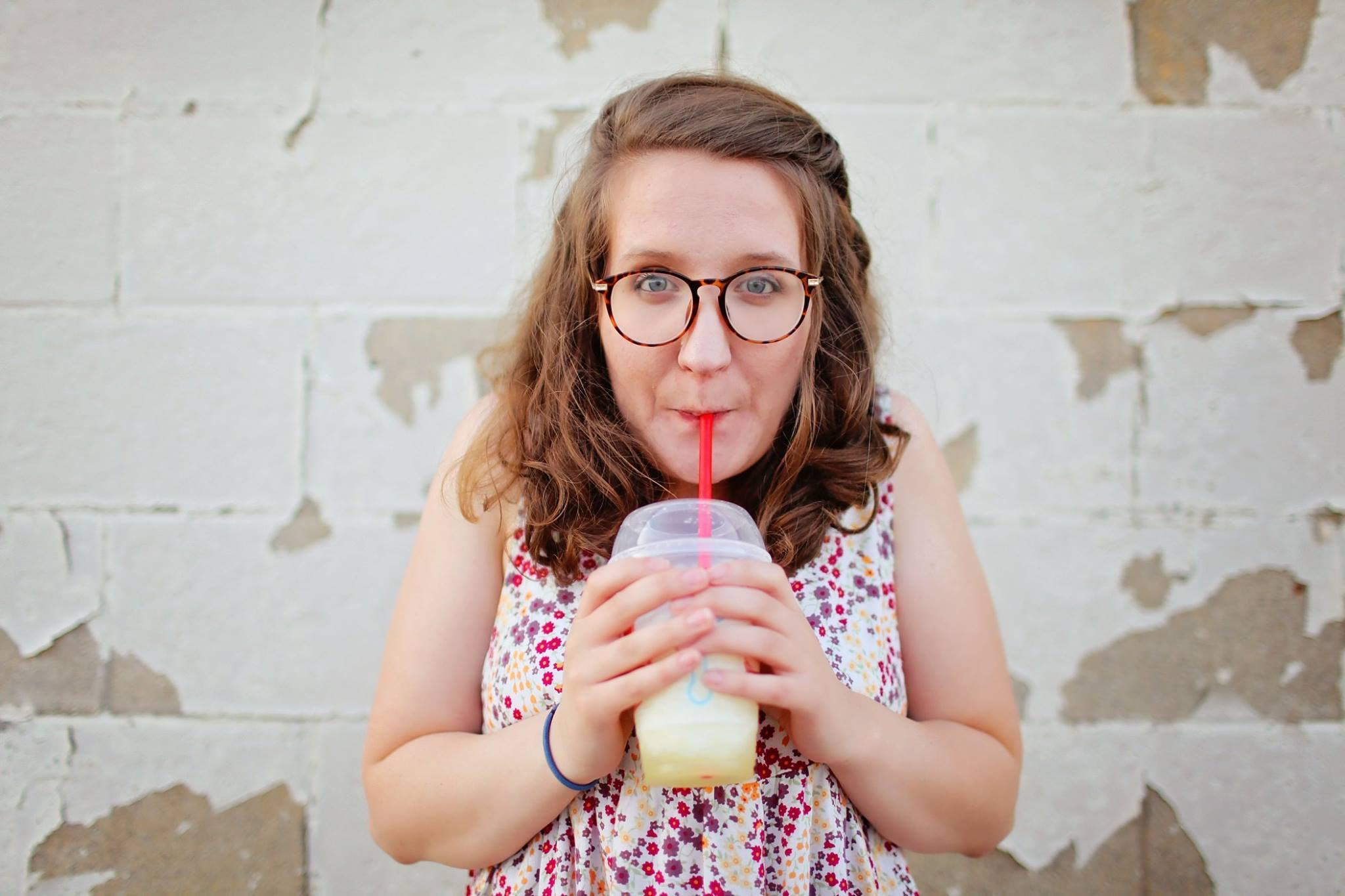 Woman in black framed eyeglasses drinking photo