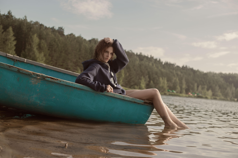 Woman in black hoodie in teal canoe in body of water photo