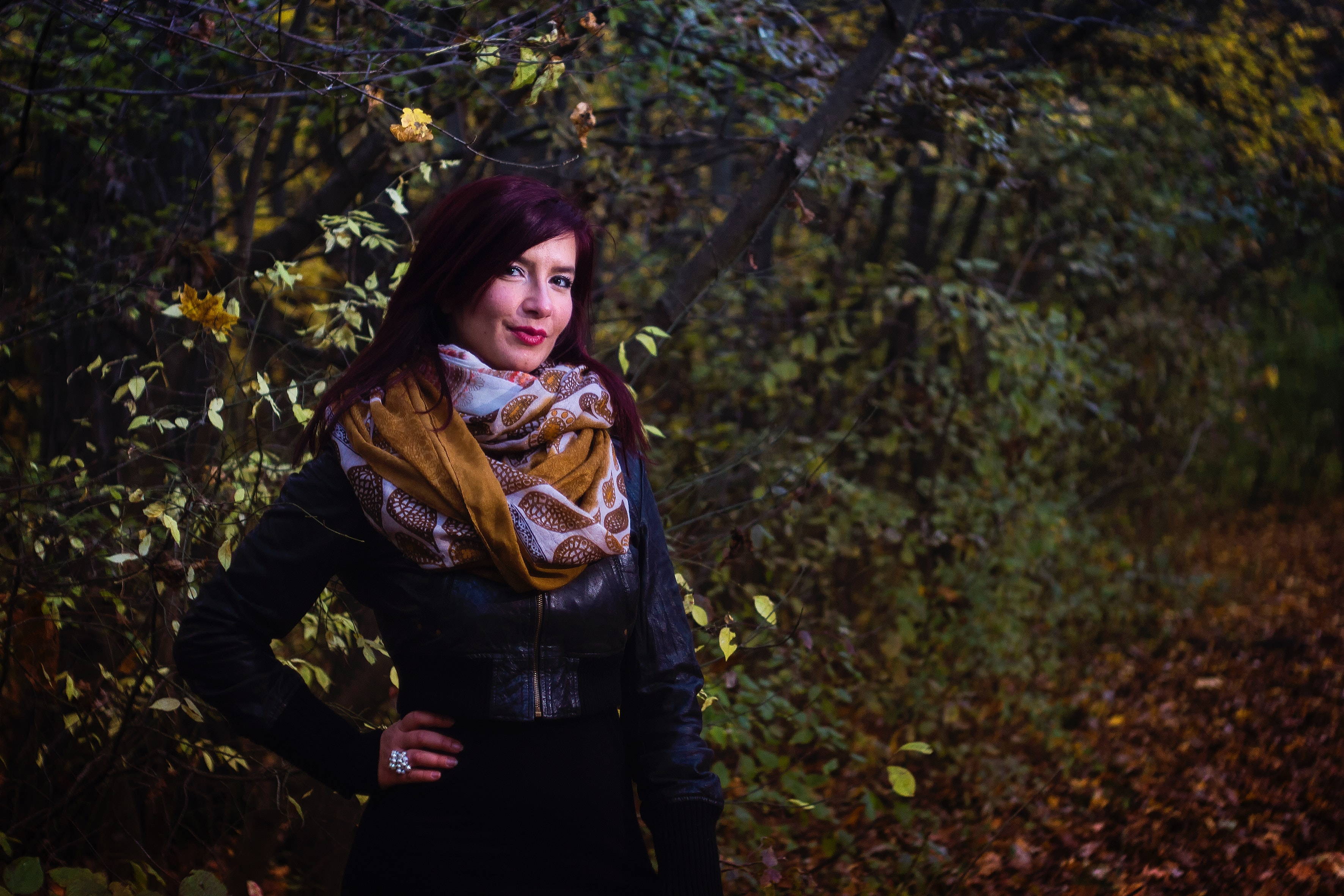 Woman in black leather jacket beside trees photo