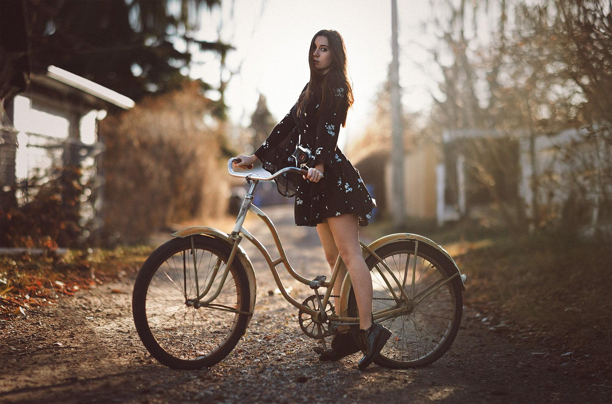 Woman riding on brown beach cruiser bike standing on brown road ...