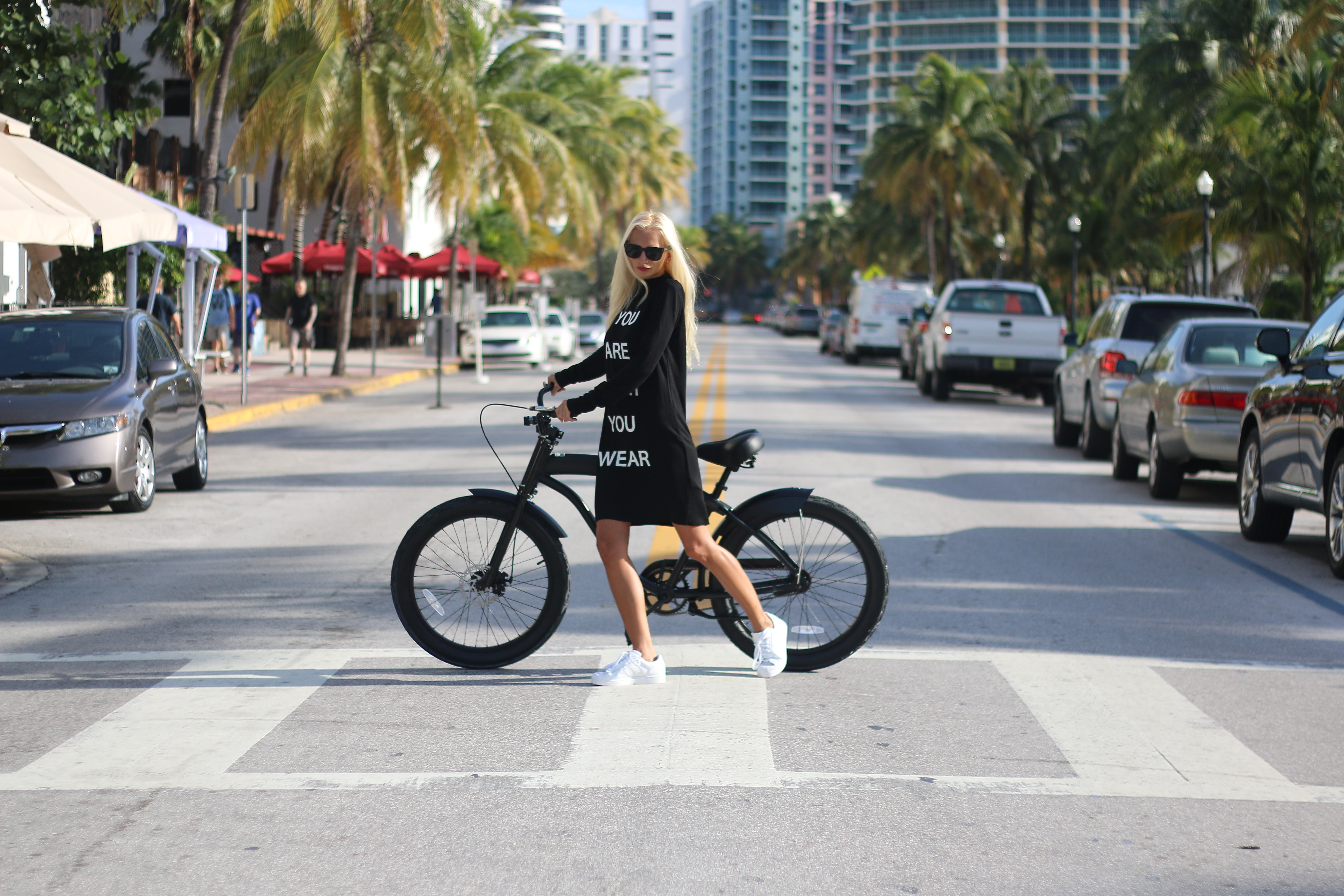 Woman in black long sleeve shirt holding bicycle photo