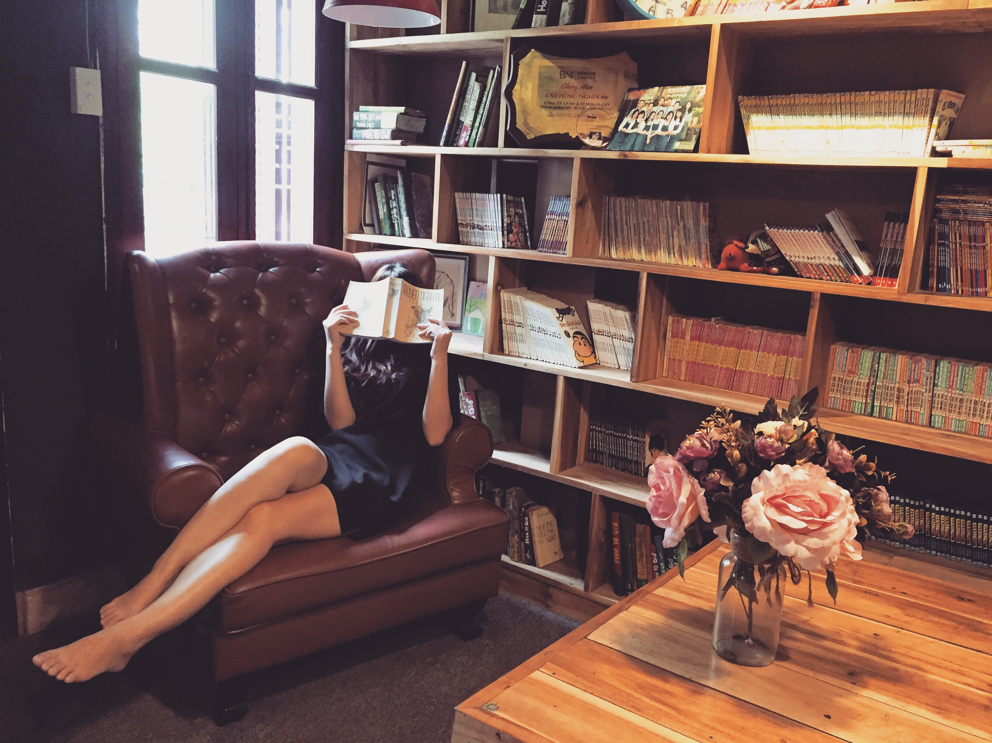 Woman in black mini dress sitting on brown leather tufted sofa chair beside brown wooden book shelf photo