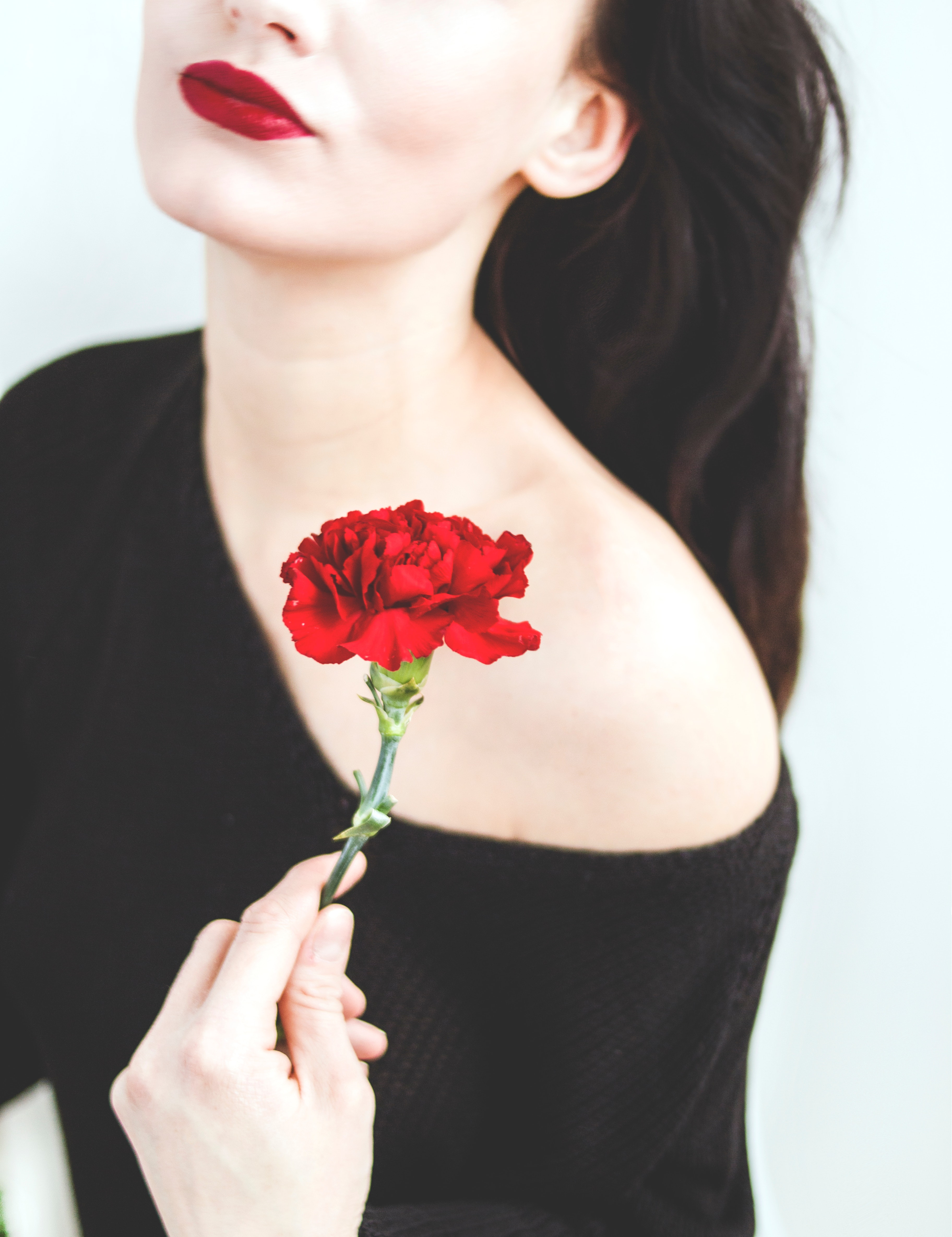 Woman in black one-shoulder top holding red carnation photo