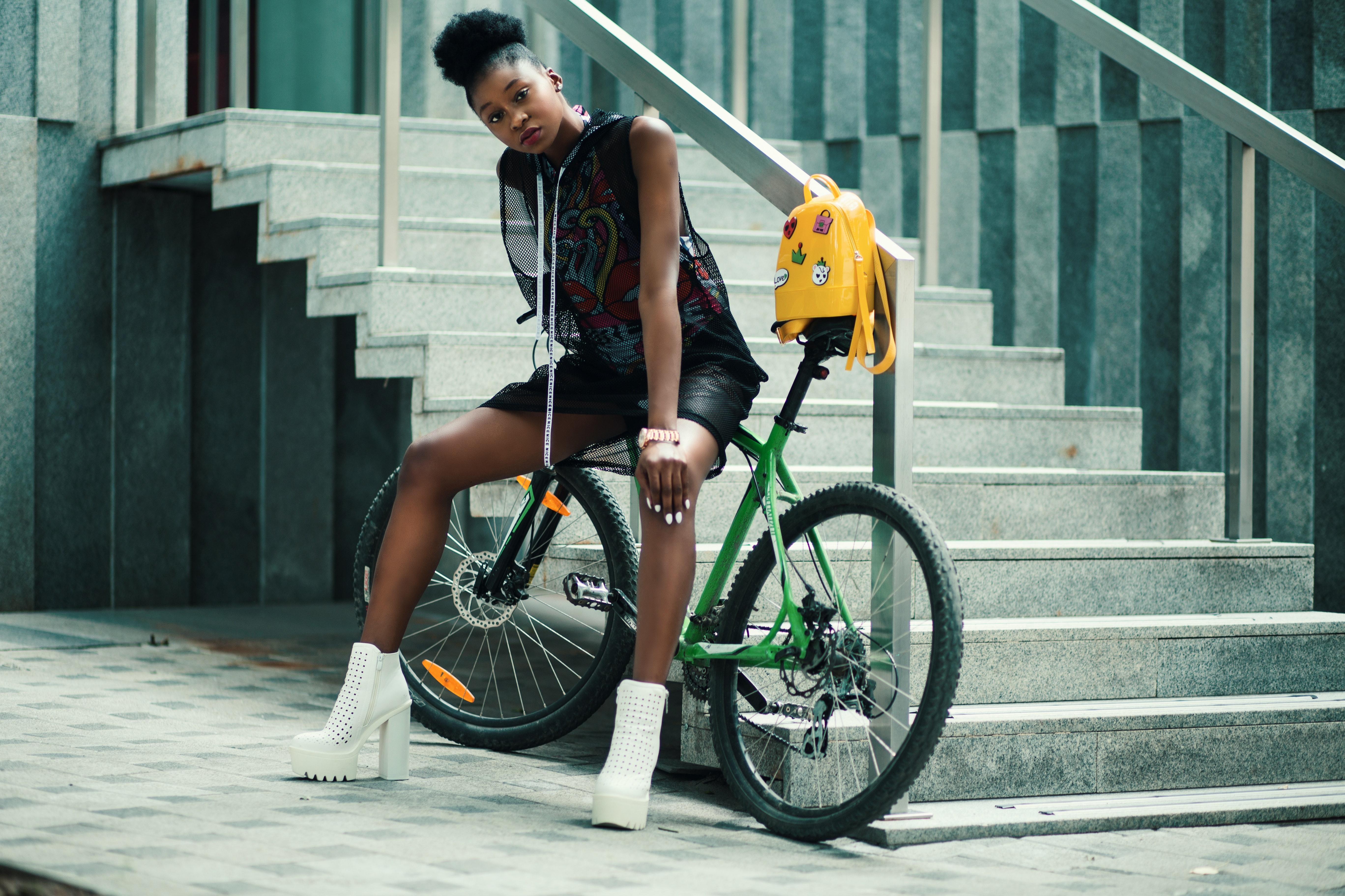Woman in black sleeveless dress sitting on green bike photo