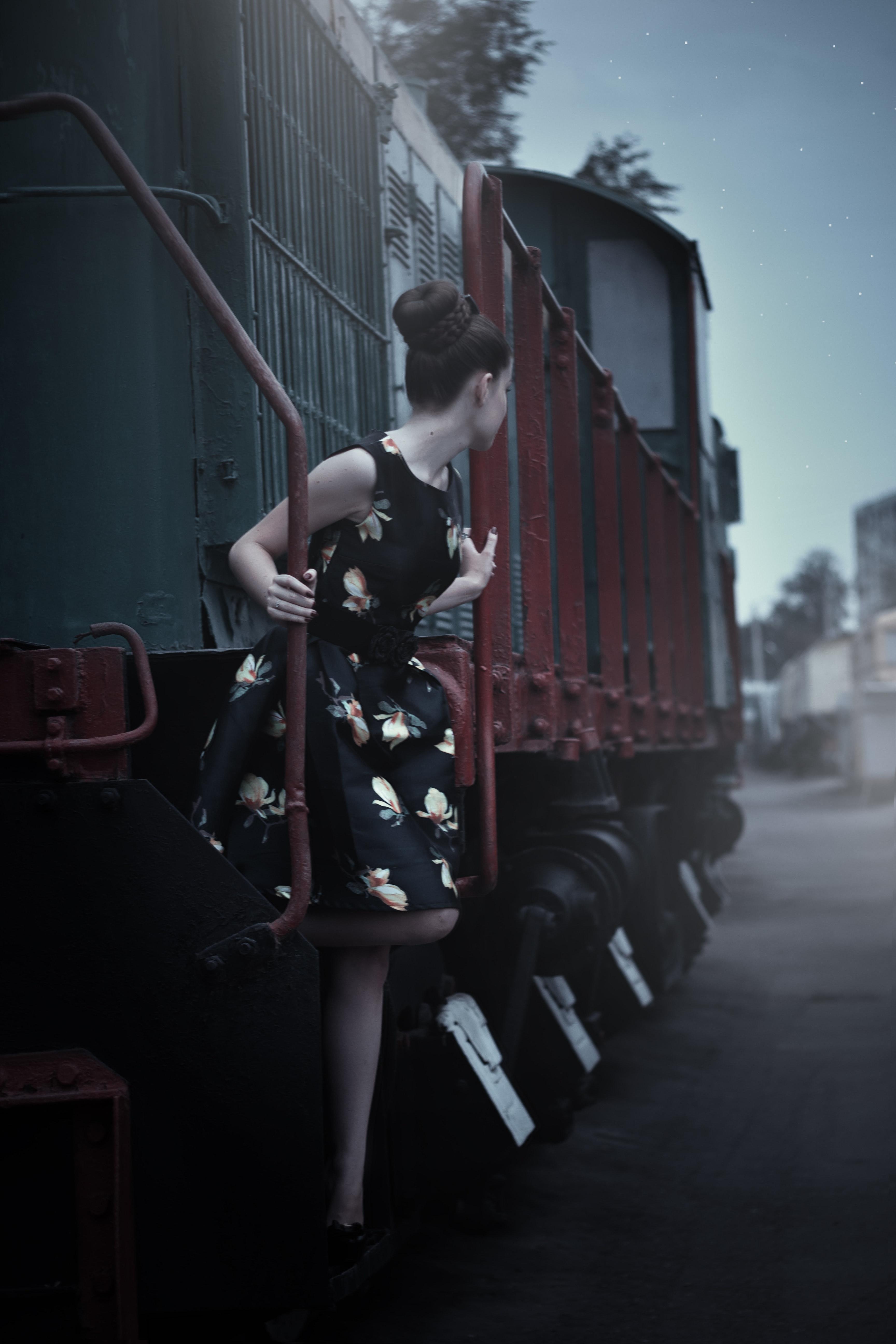 Woman in black sleeveless dress standing beside train photo