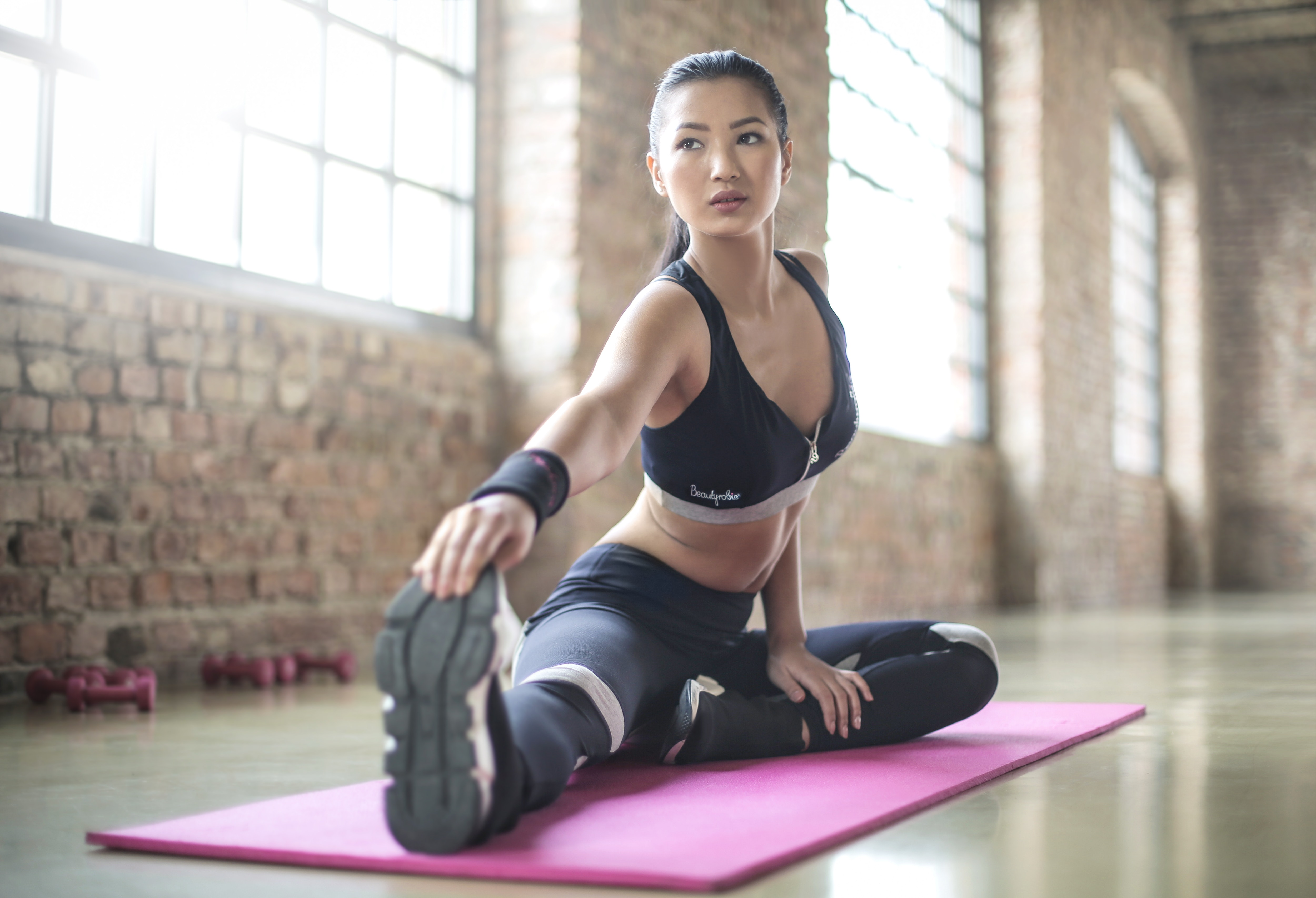 Woman in black sports brassiered and black pants doing yoga photo