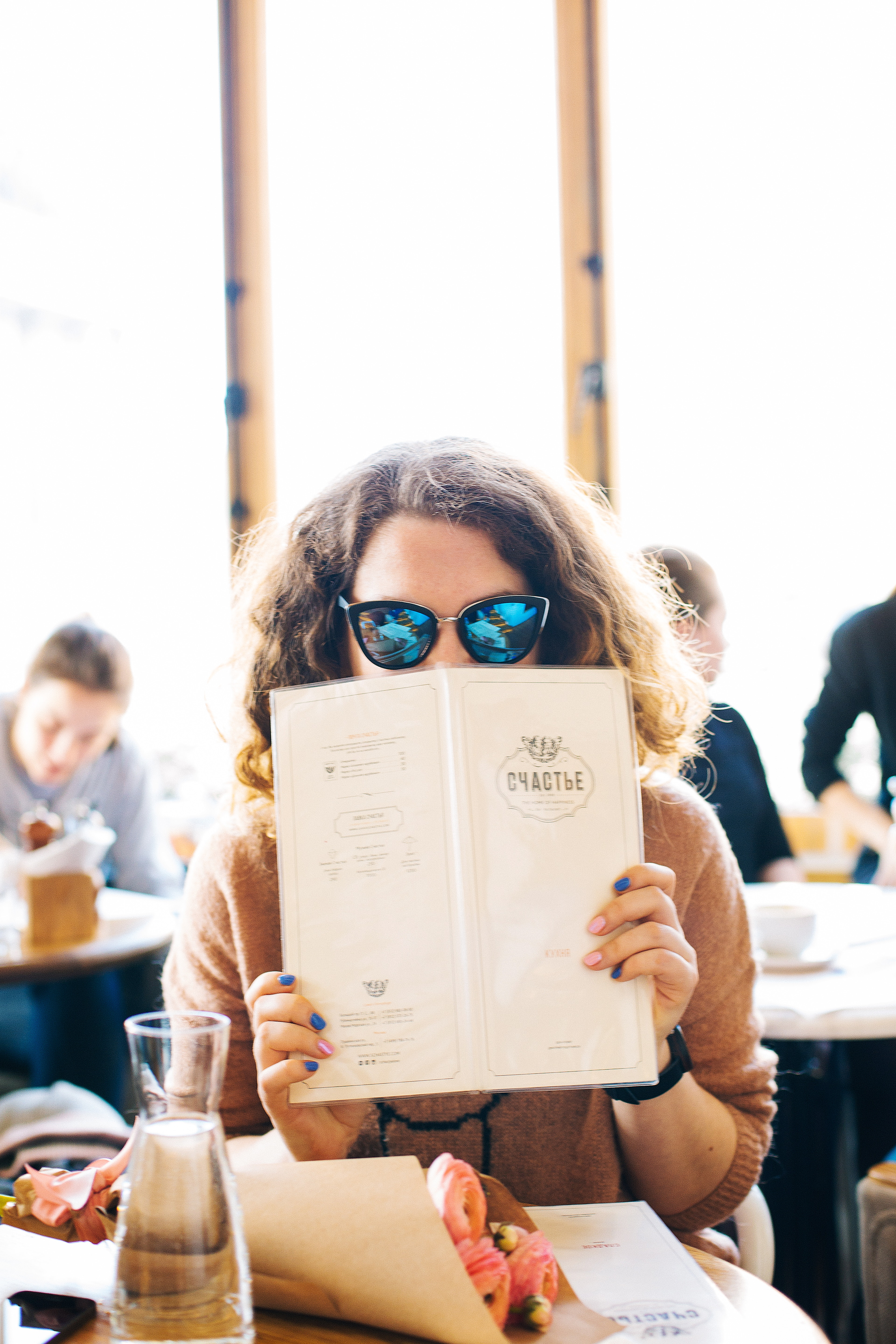 Woman in black sunglasses holding menu photo