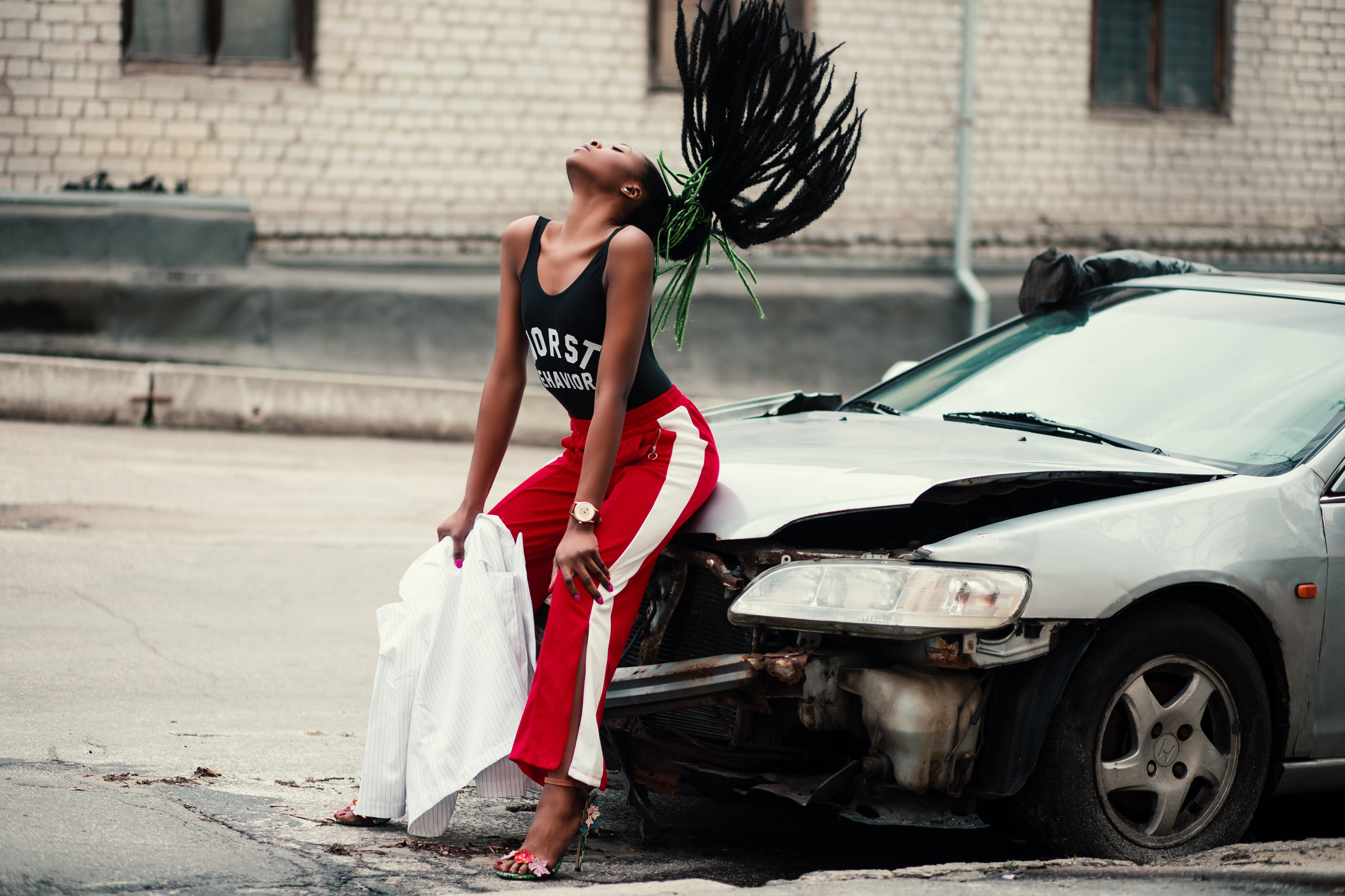 Woman in black tank top sitting in front of car photo