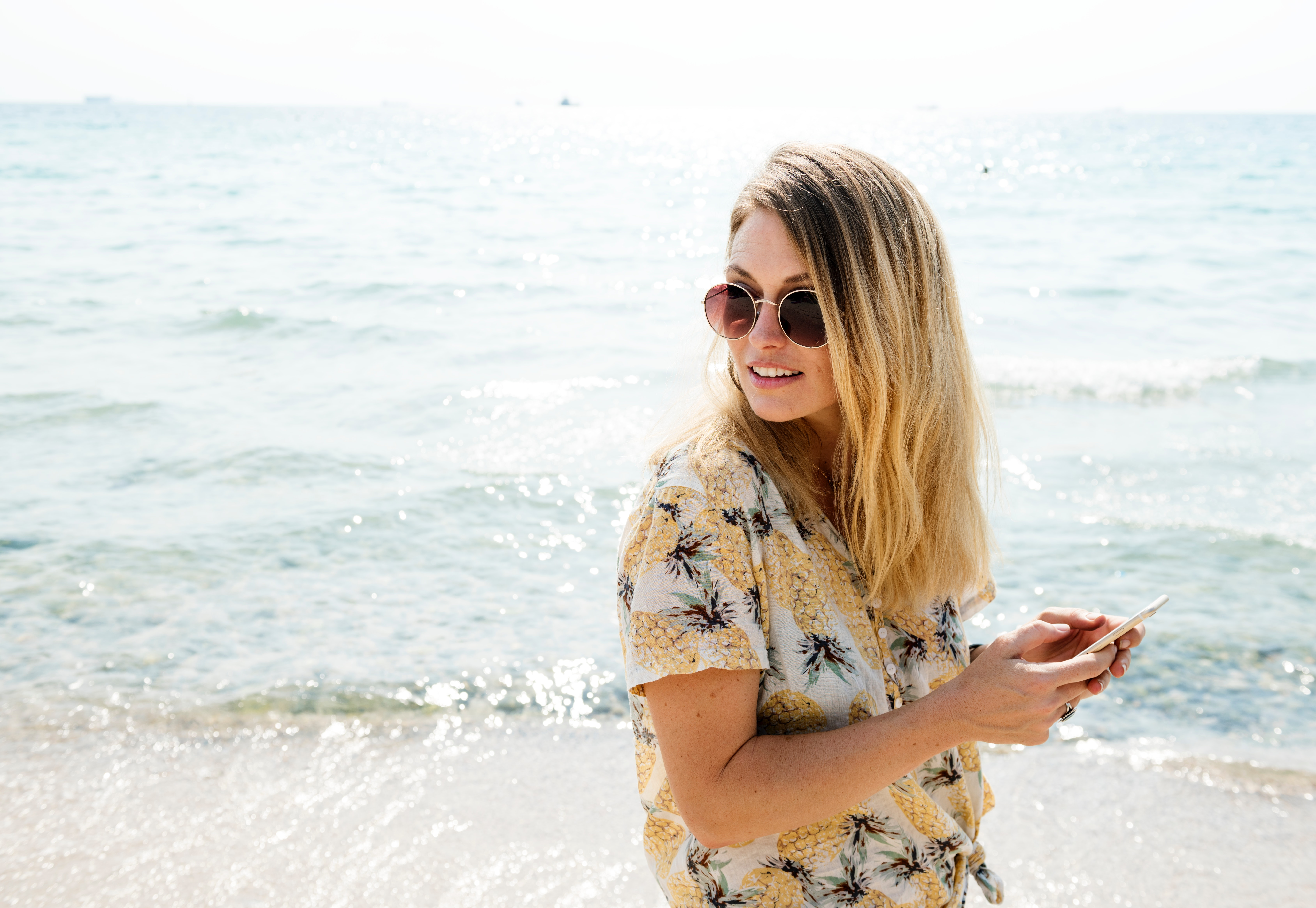 Woman in black yellow and white floral button-up shirt holding smartphone wearing aviator sunglasses near body of water photo