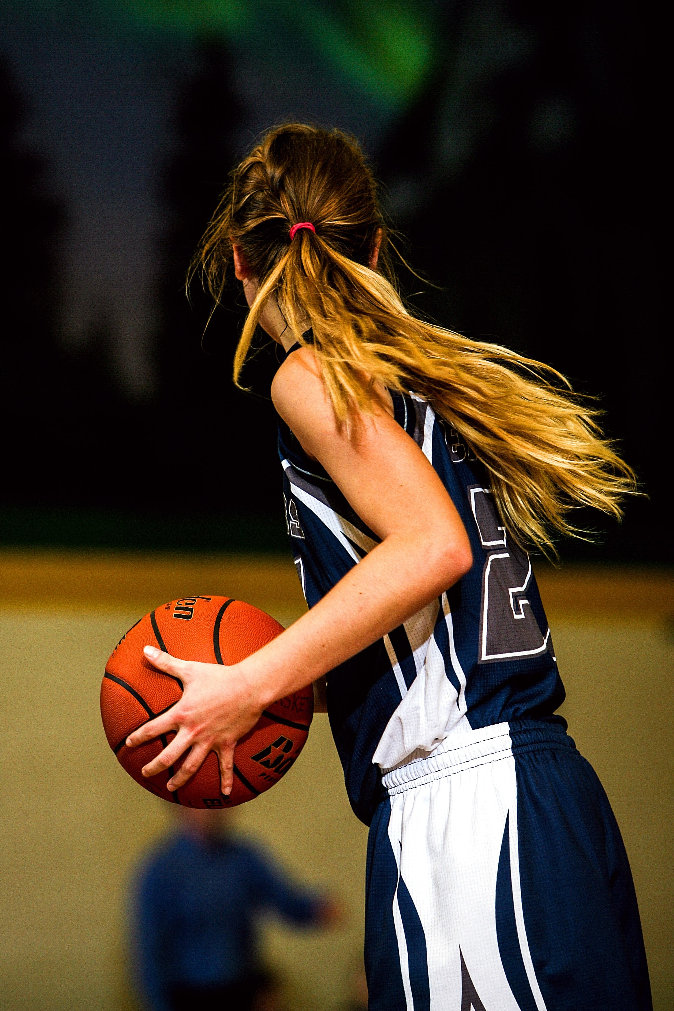 Woman in blue and white basketball jersey holding brown basketball photo