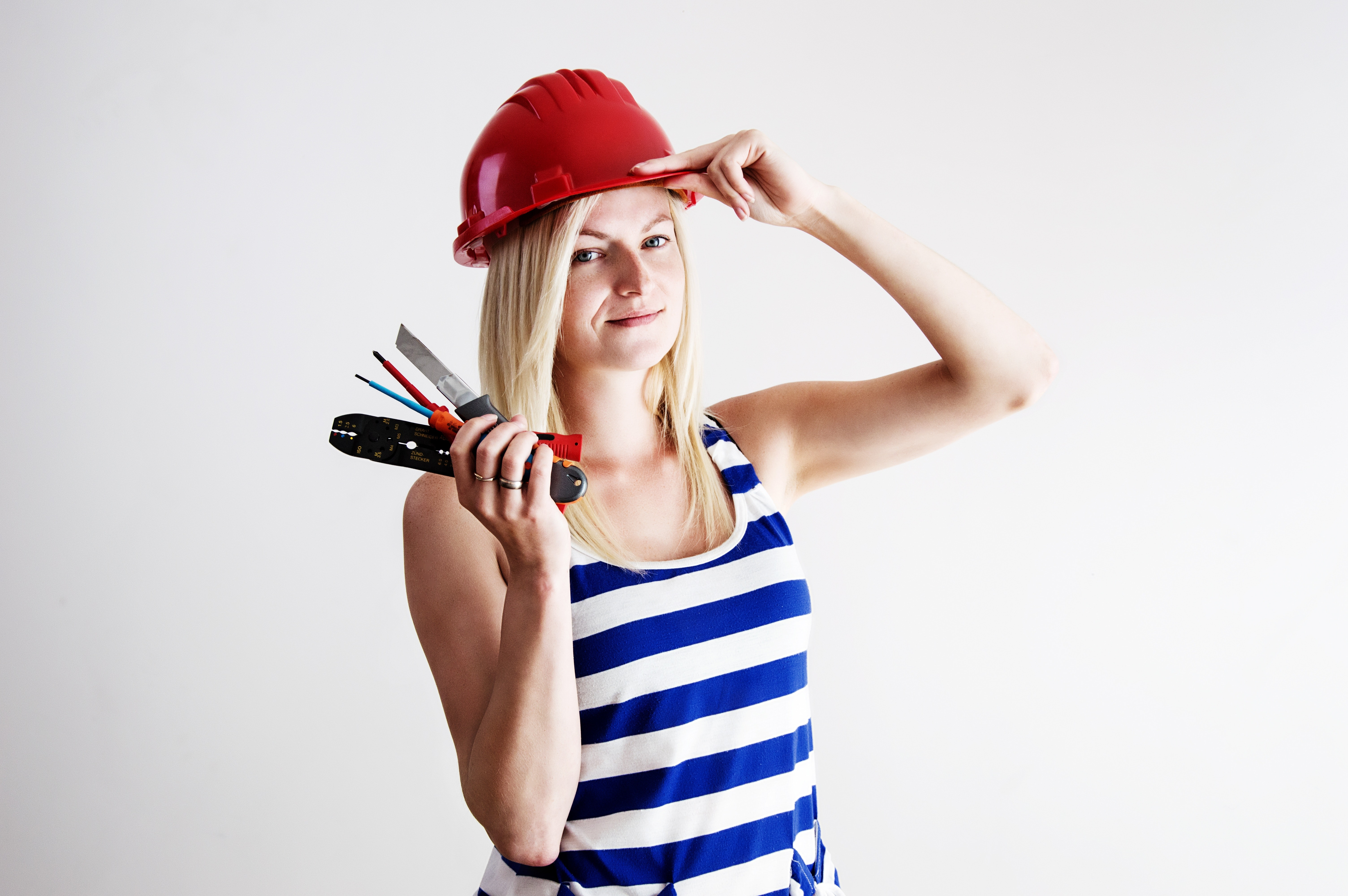 Woman in blue and white tank top wearing red hard hat photo