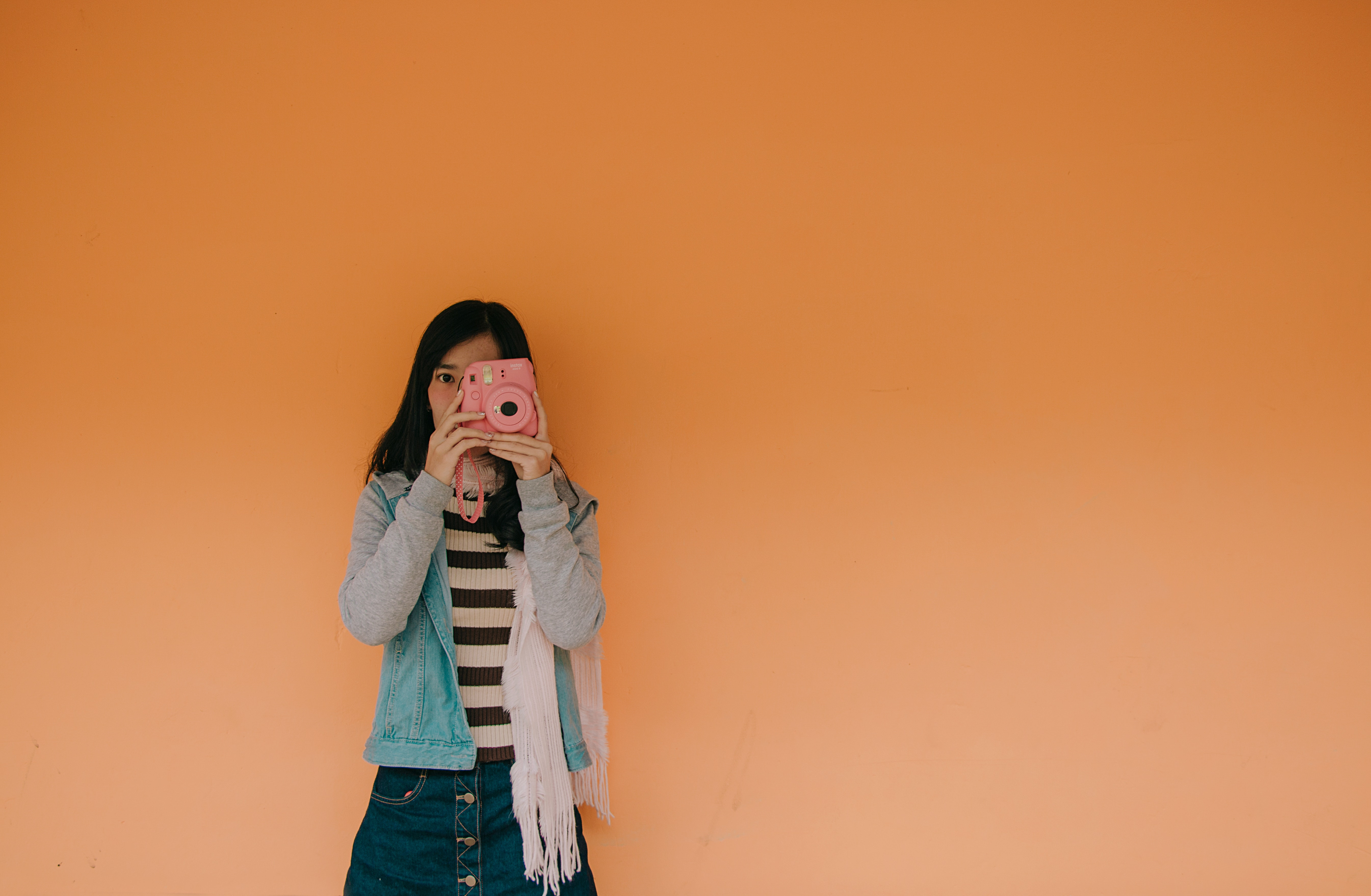 Woman in blue jacket holding pink fujifilm instax camera photo