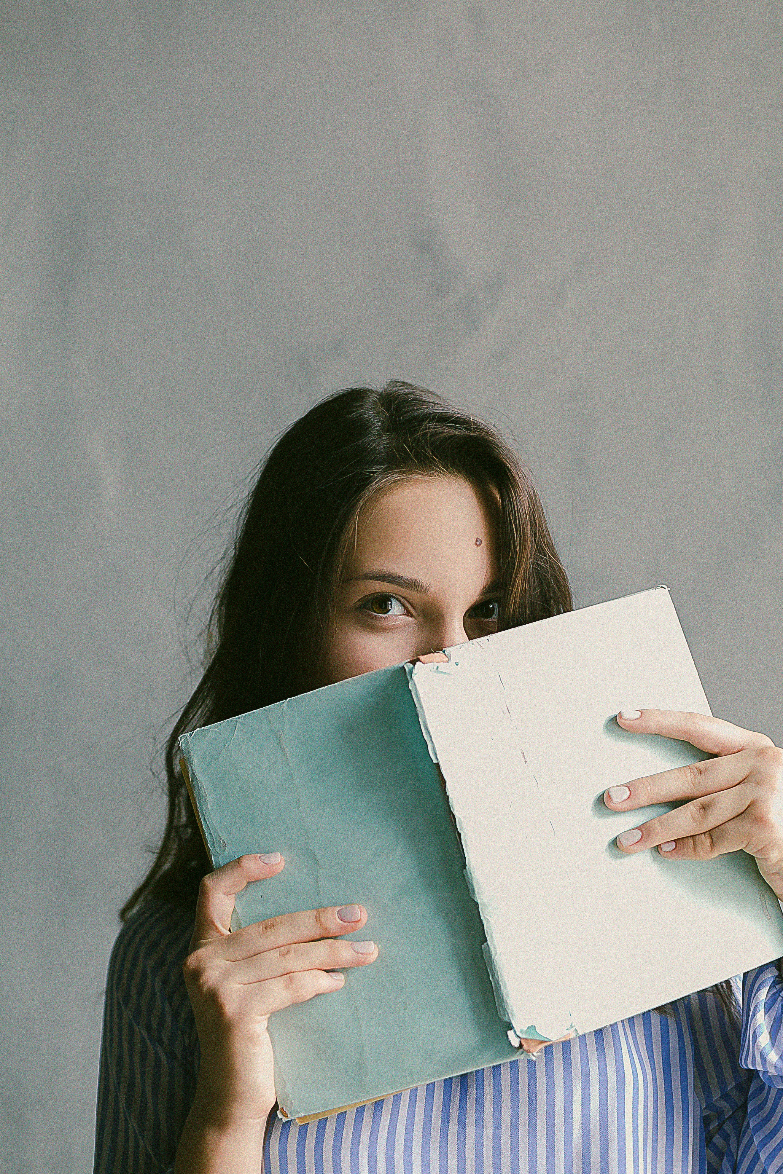 Woman in blue striped flannel shirt holding a book indoors photo