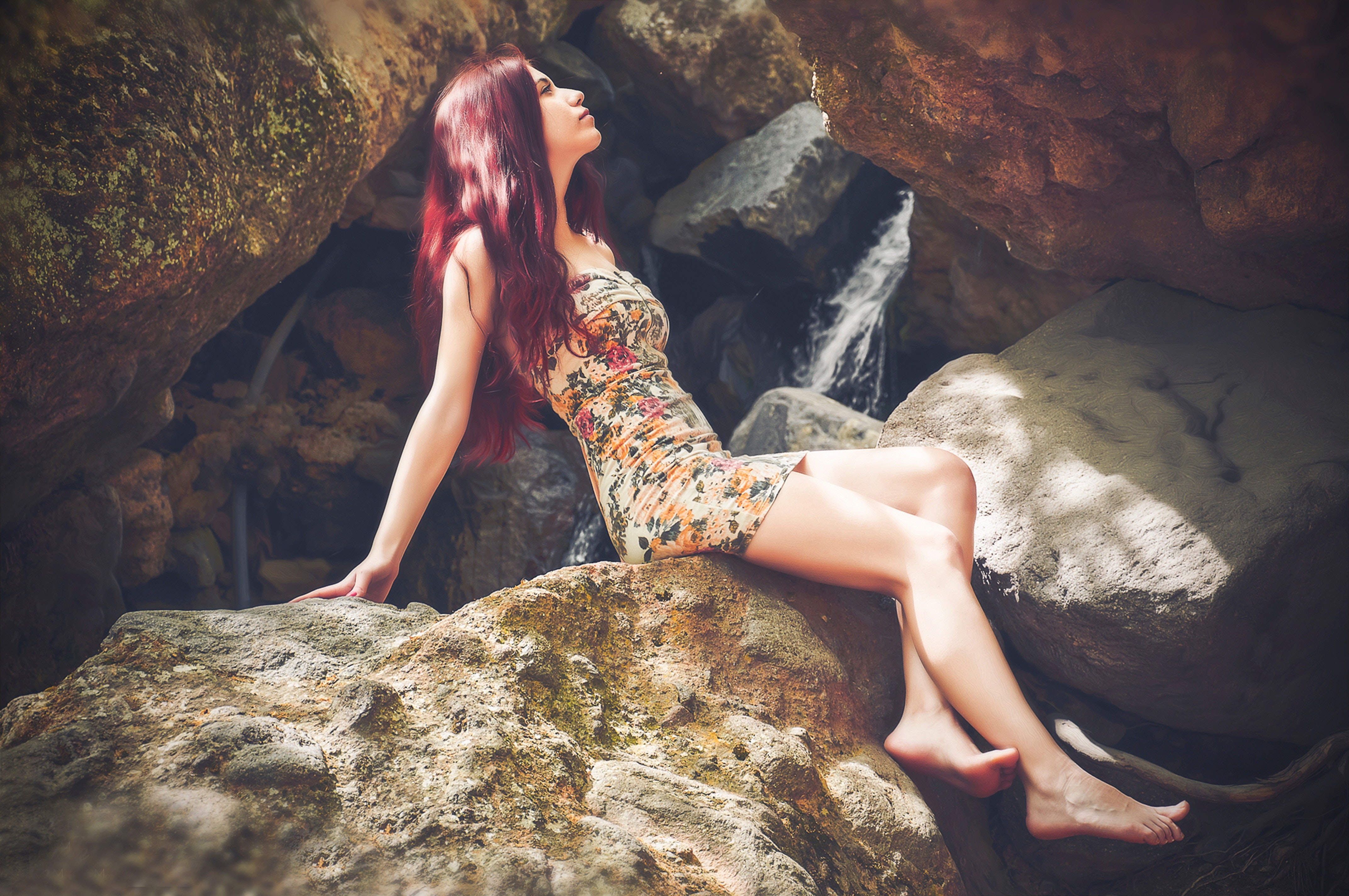 Woman in bodycon mini dress sitting on boulder photo