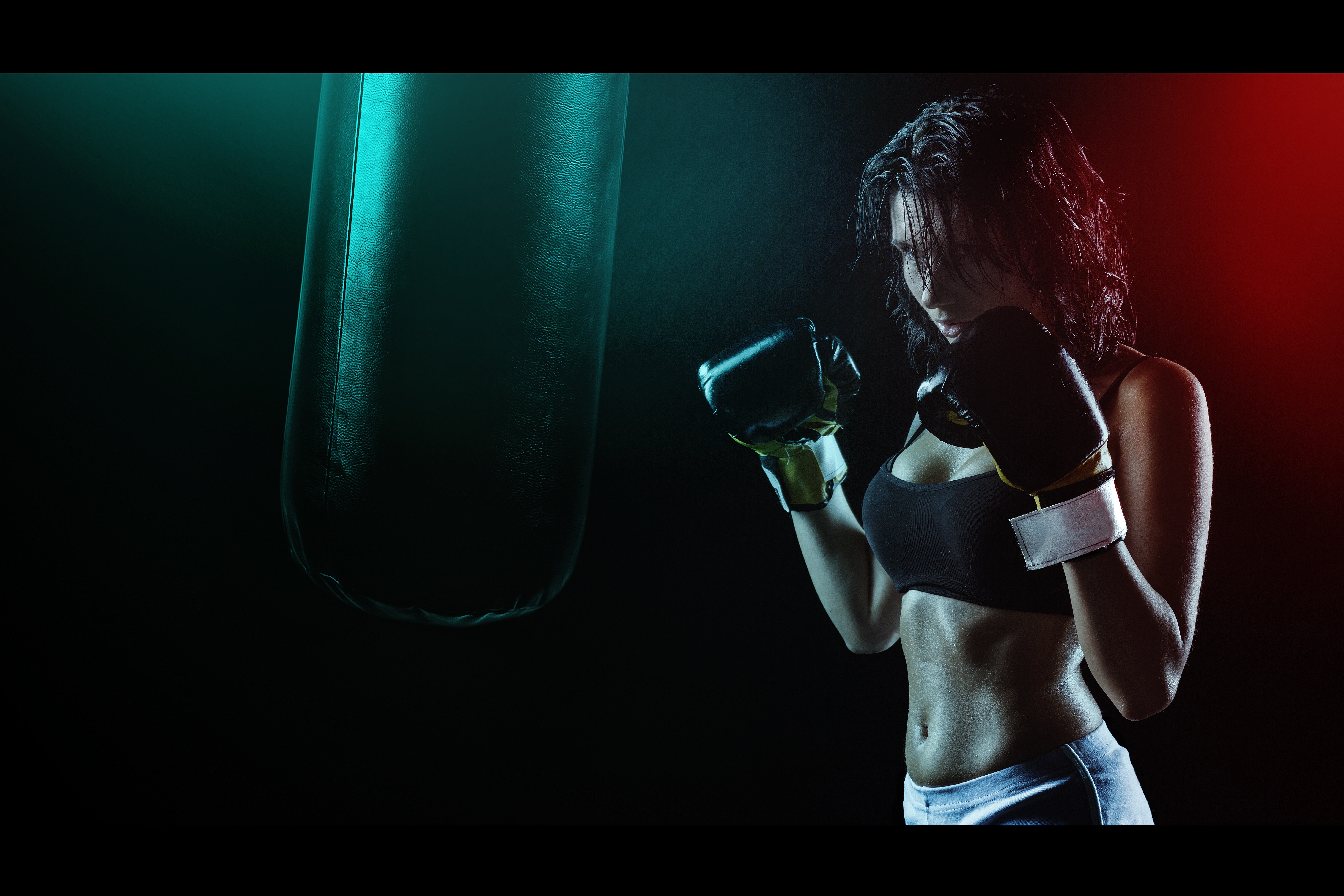 Woman in boxing gloves with sports bra posing boxing style in front of punching bag photo