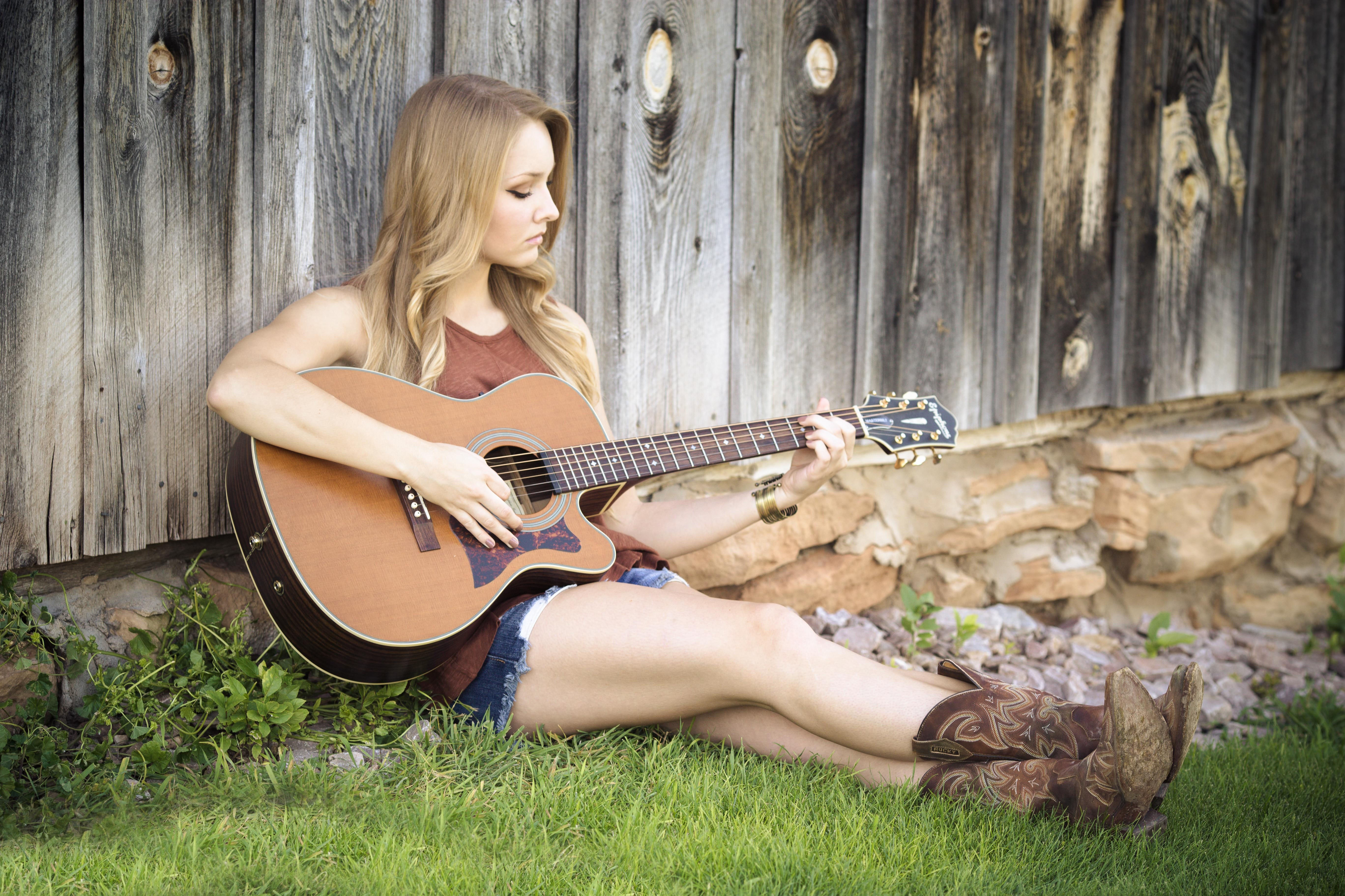 Woman in brown tank top with acoustic guitar sitting on green grass beside brown wooden fence photo