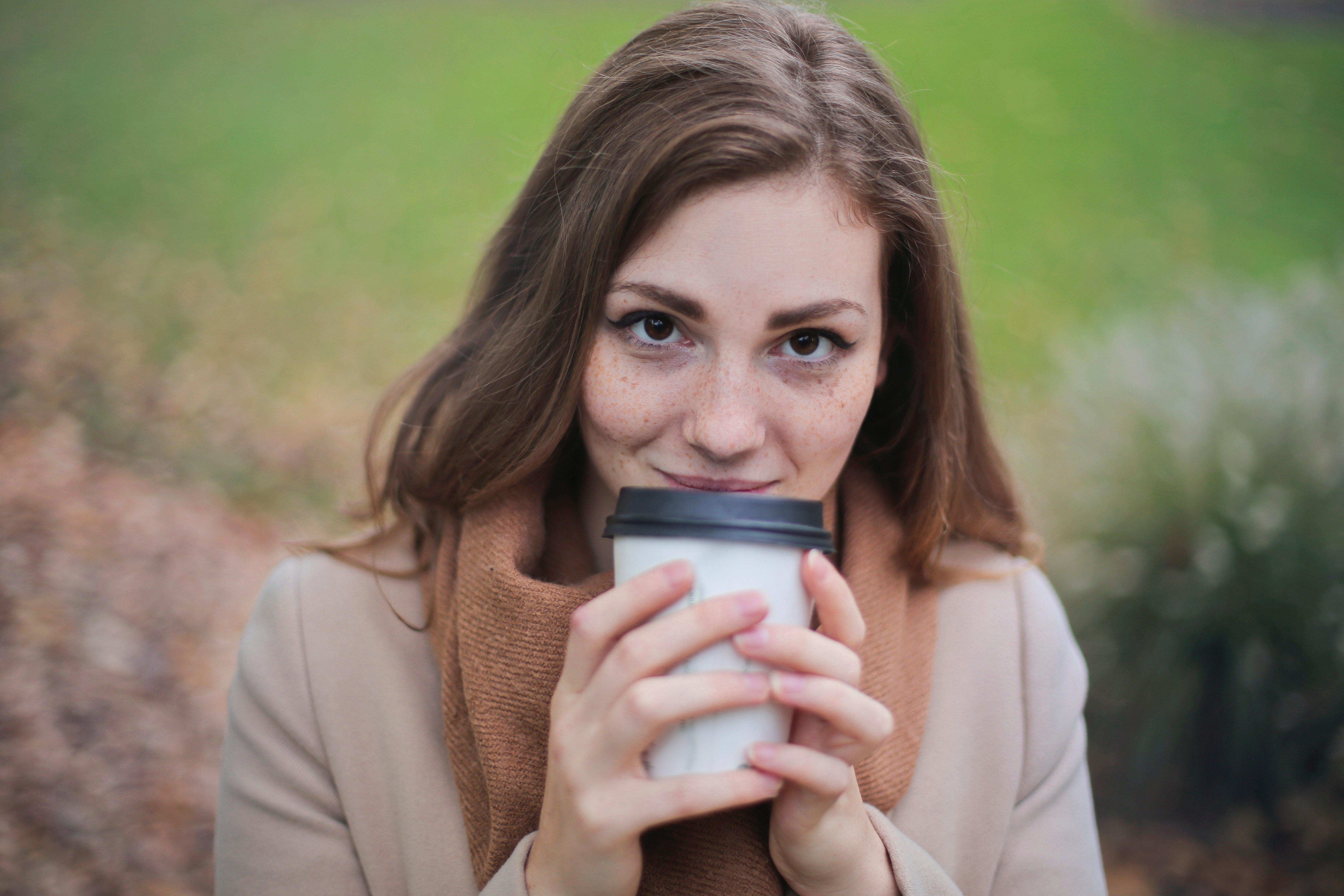 Woman in brown top and scarf holding a white and black travel cup outside photo