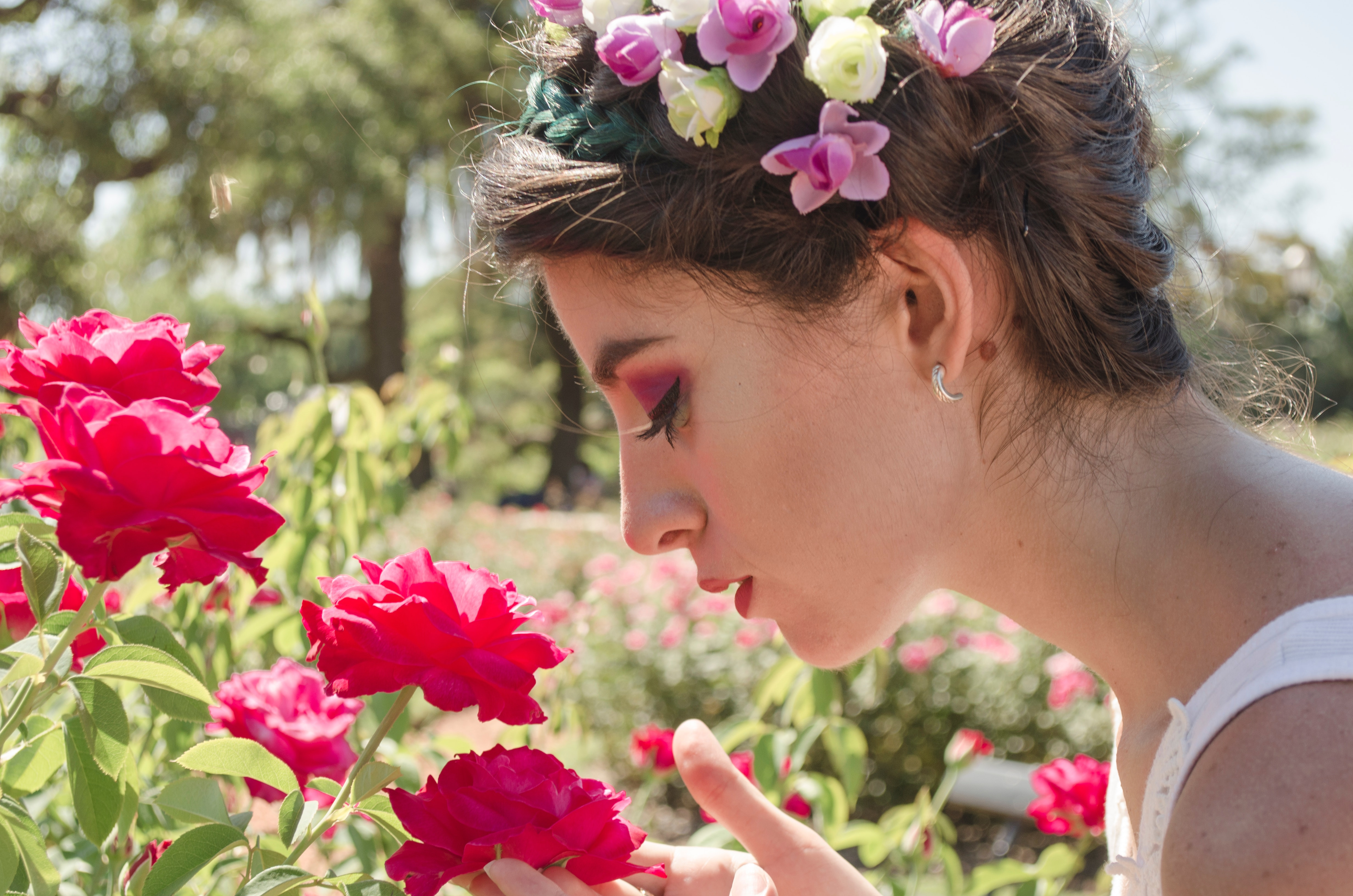 Free photo woman in floral headdress sniffing on red flowers woman in floral headdress sniffing on red flowers photo izmirmasajfo