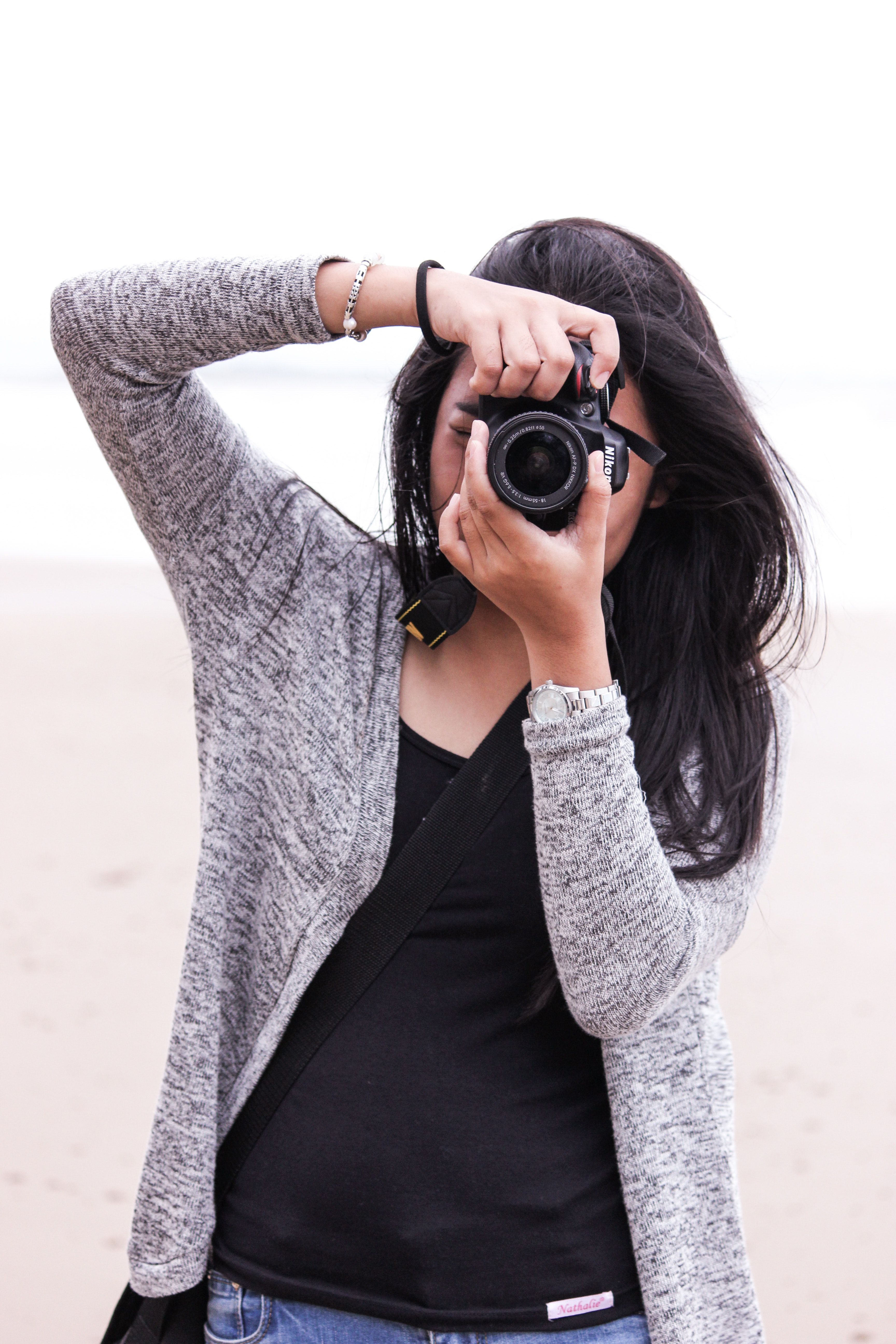 Woman in gray cardigan and black shirt holding black dslr camera photo