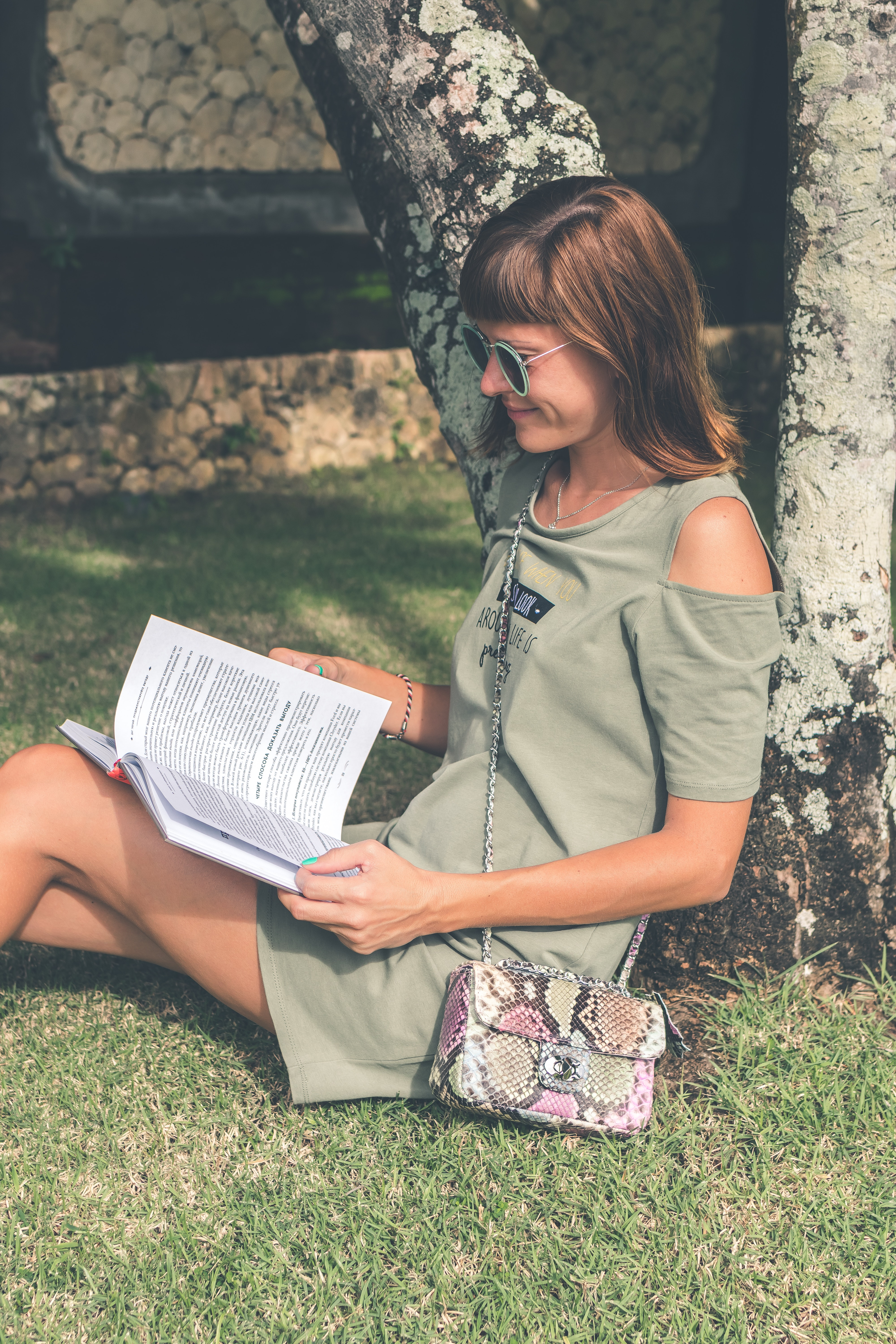 Woman in gray dress reading book at daytime photo