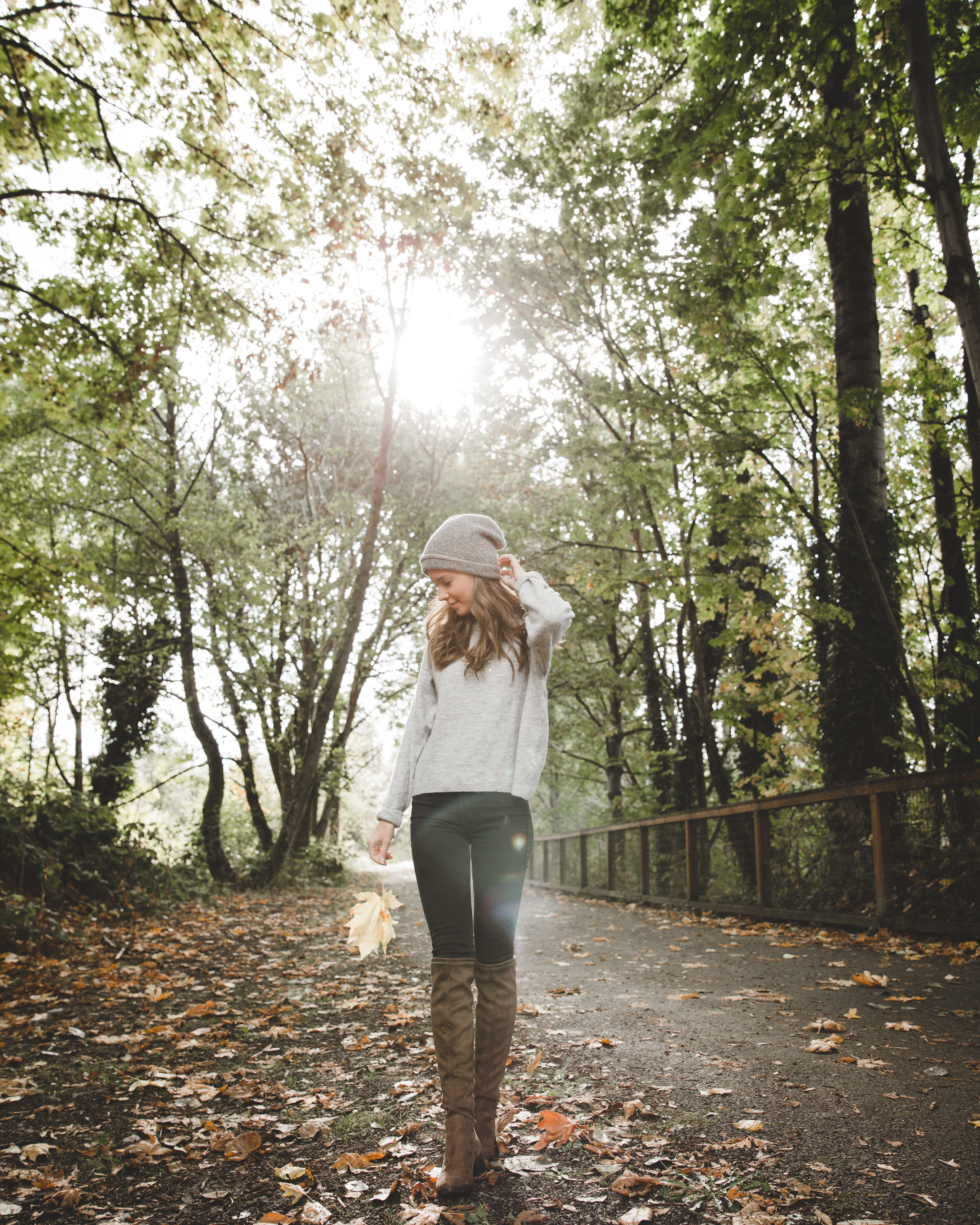 Woman in gray sweater standing between forest trees photo