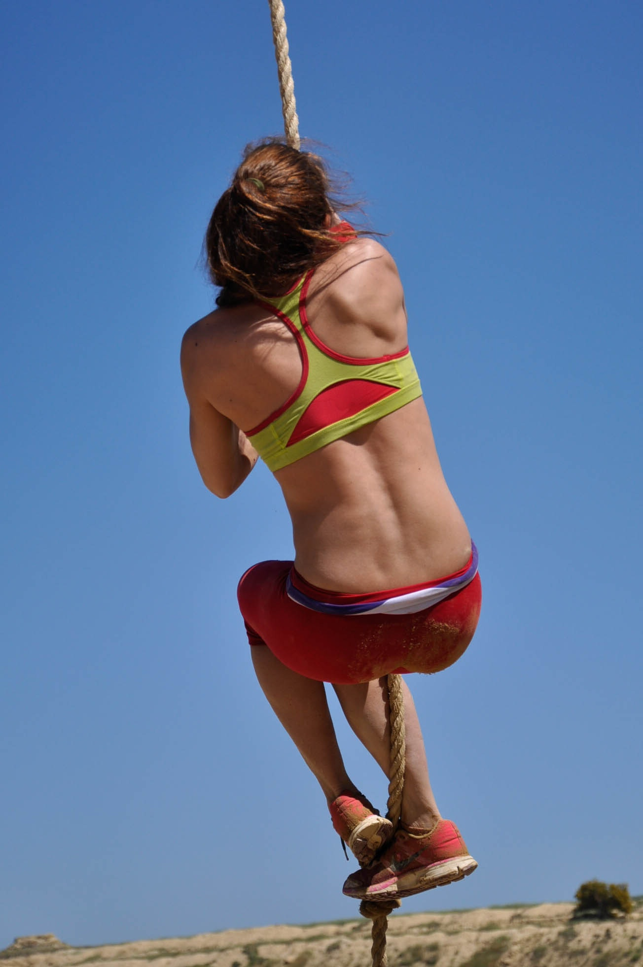 Woman in green and red sports bra holding rope during daytime photo