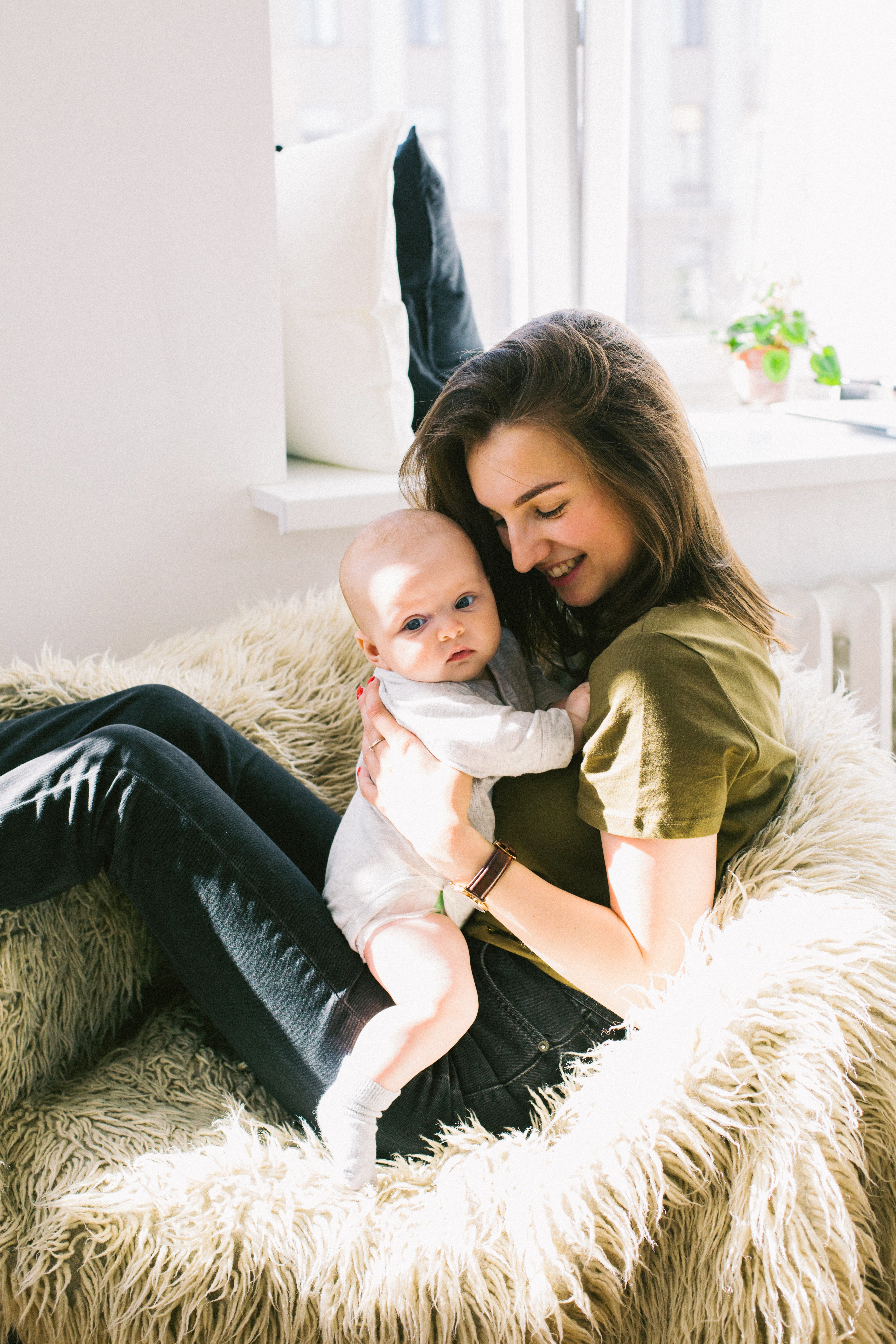 Woman in green shirt holding baby while sitting photo
