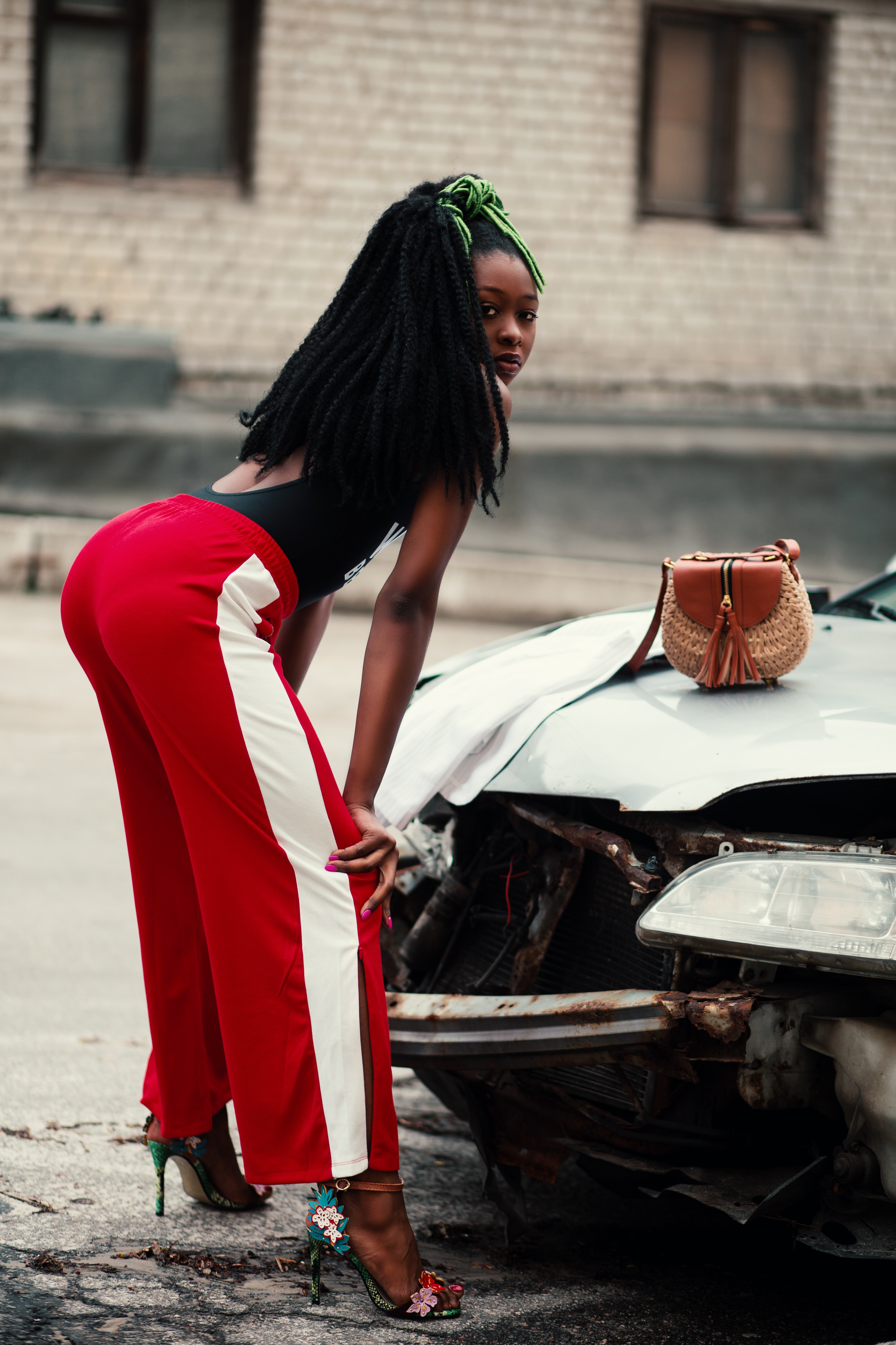 Woman in maroon and white pants leaning in front of broken car photo