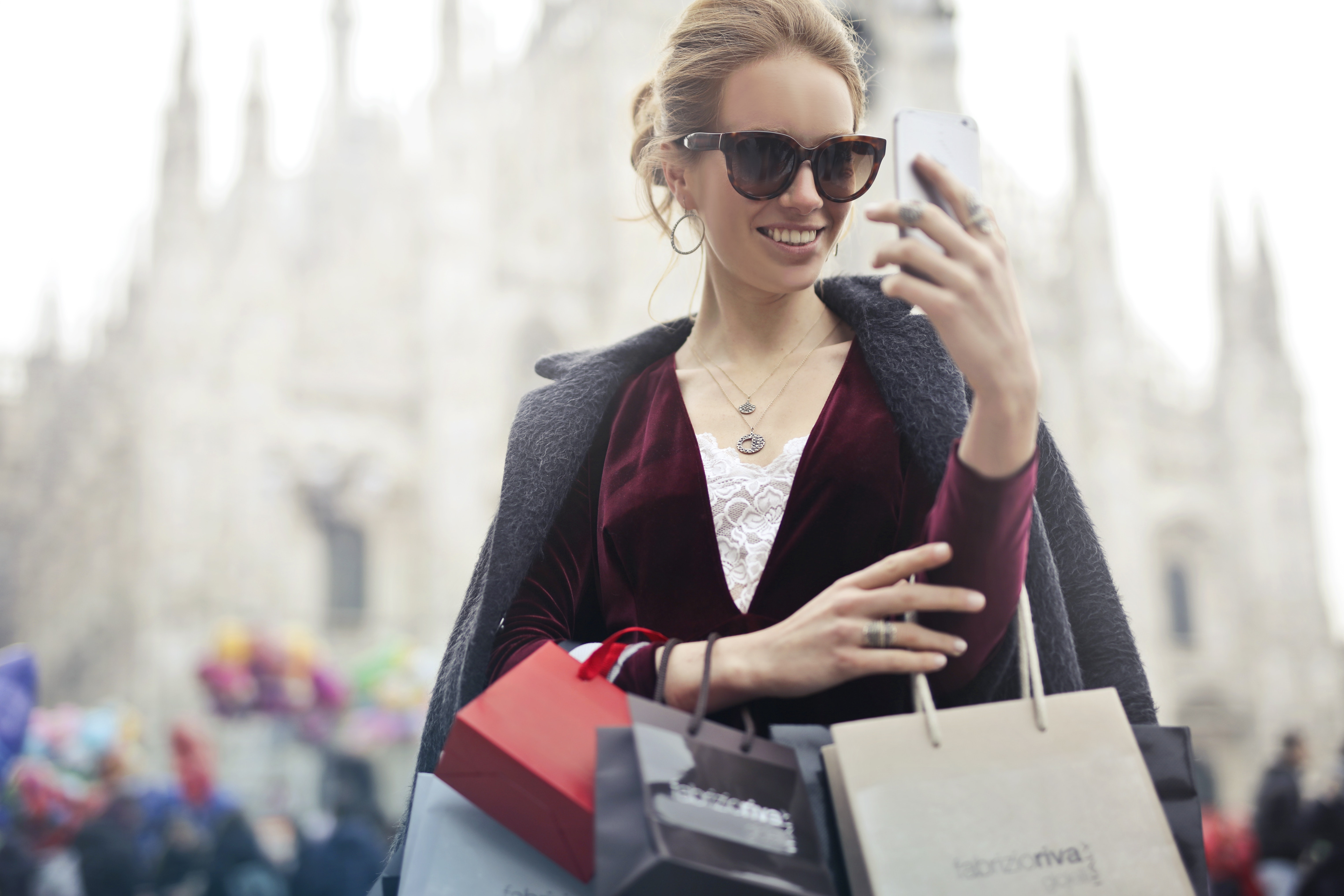 Woman in Maroon Long-sleeved Top Holding Smartphone With Shopping Bags at Daytime, Adult, Photo, Wear, Technology, HQ Photo