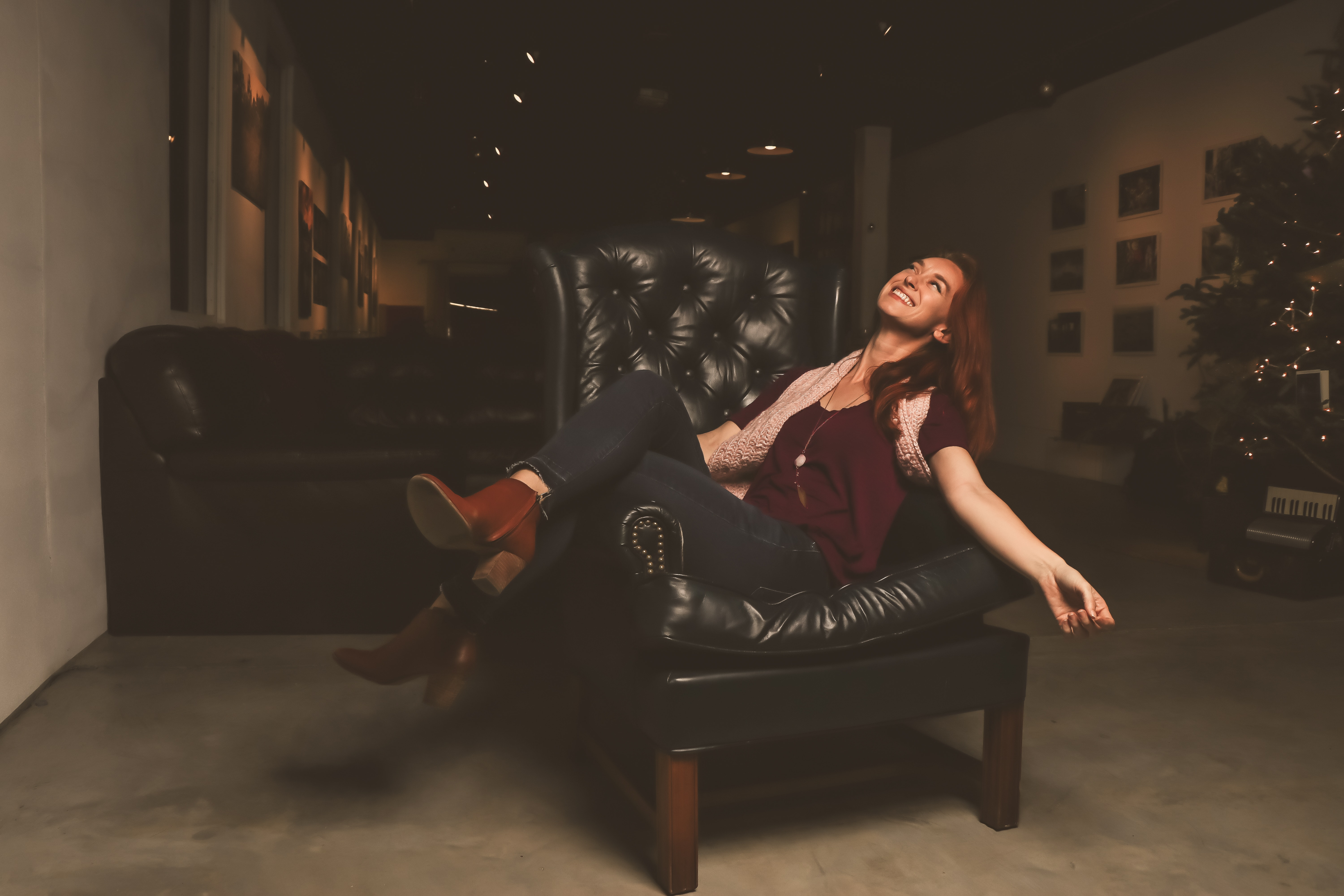 Woman in maroon scoop-neck shirt sitting on black leather sofa chair photo